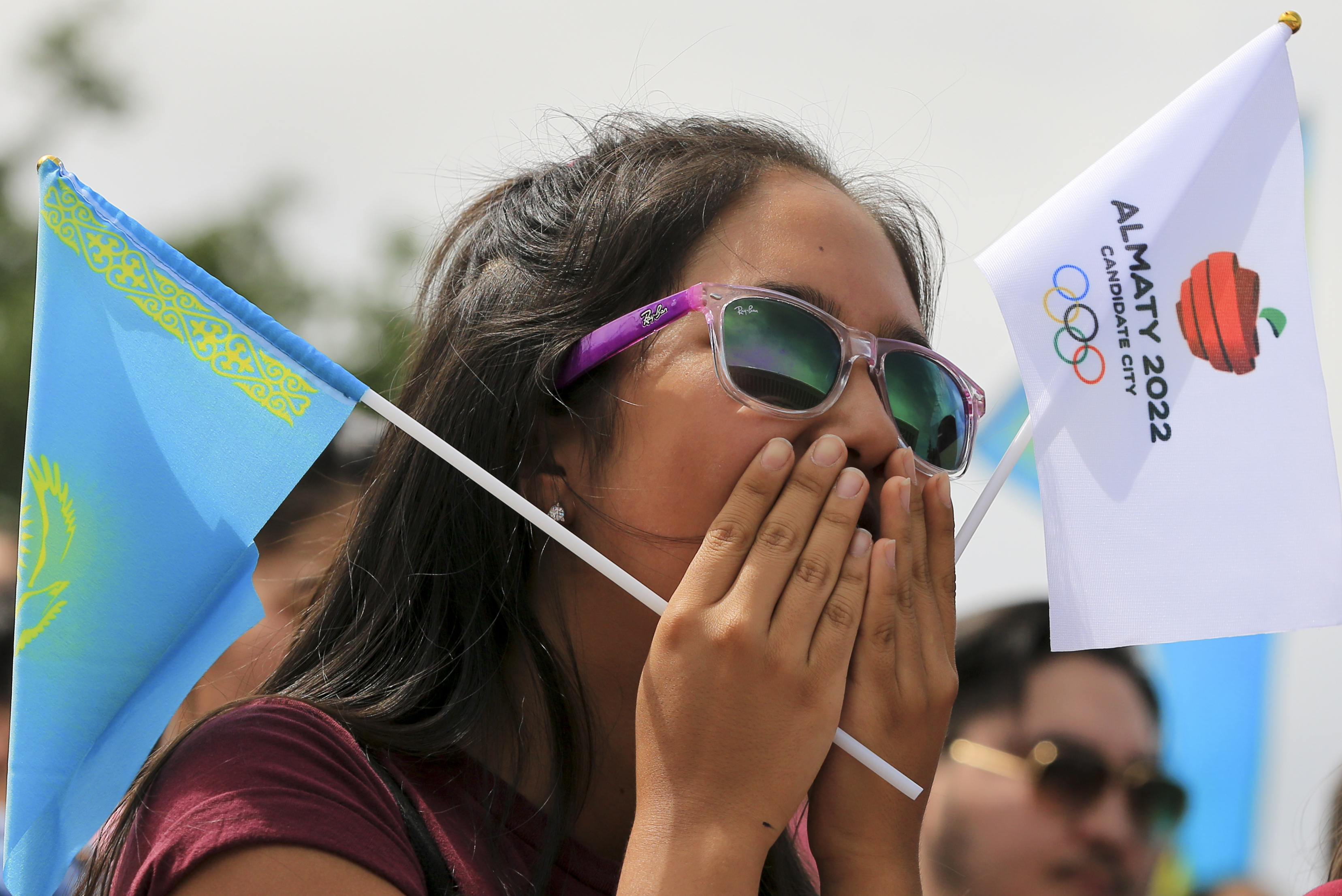A woman reacts as she watches the Olympic vote in Almaty, Kazakhstan, Friday, July 31, 2015. Beijing has been selected to host the 2022 Winter Olympics, becoming the first city awarded both the winter and summer games. Beijing defeated Almaty, Kazakhstan,