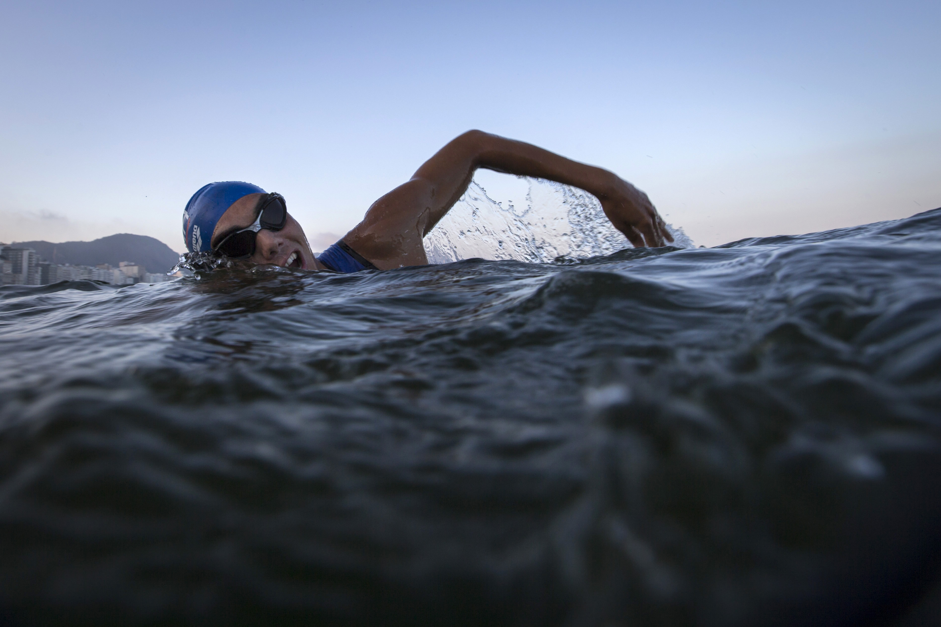 """A triathlete swims in the waters of Copacabana Beach during training in Rio de Janeiro, Brazil, Friday, July 31, 2015. Triathletes swam in the waters off Copacabana despite published warnings that water in the area was """"unfit"""" for swimming. Athletes said"""