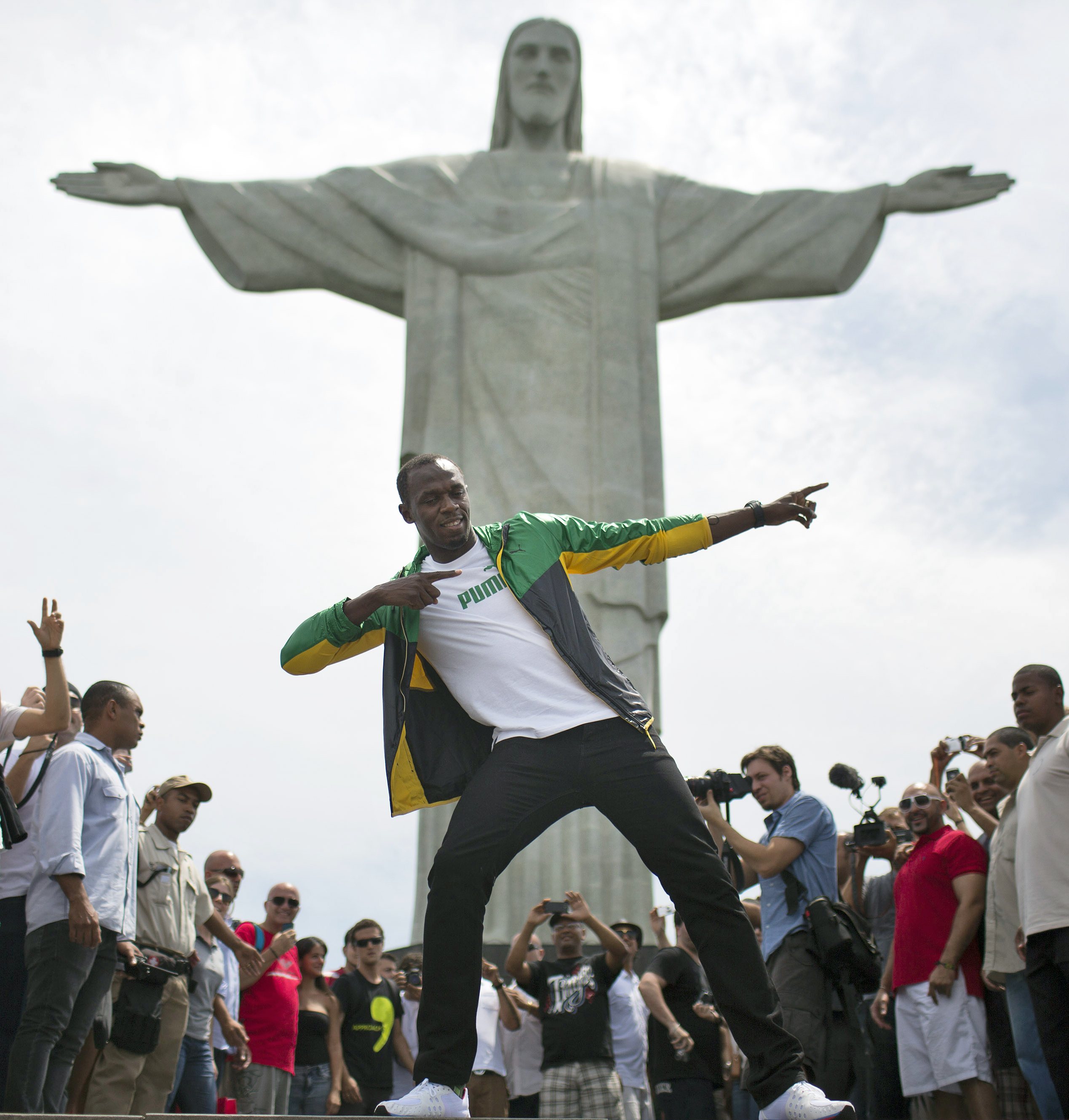 FILE - In this Oct. 23, 2012, file photo, Jamaica's Olympic gold medalist Usain Bolt poses for a photo for the benefit of the media during his visit to the Brazilian landmark Christ the Redeemer statue in Rio de Janeiro, Brazil. A year before the Rio Game