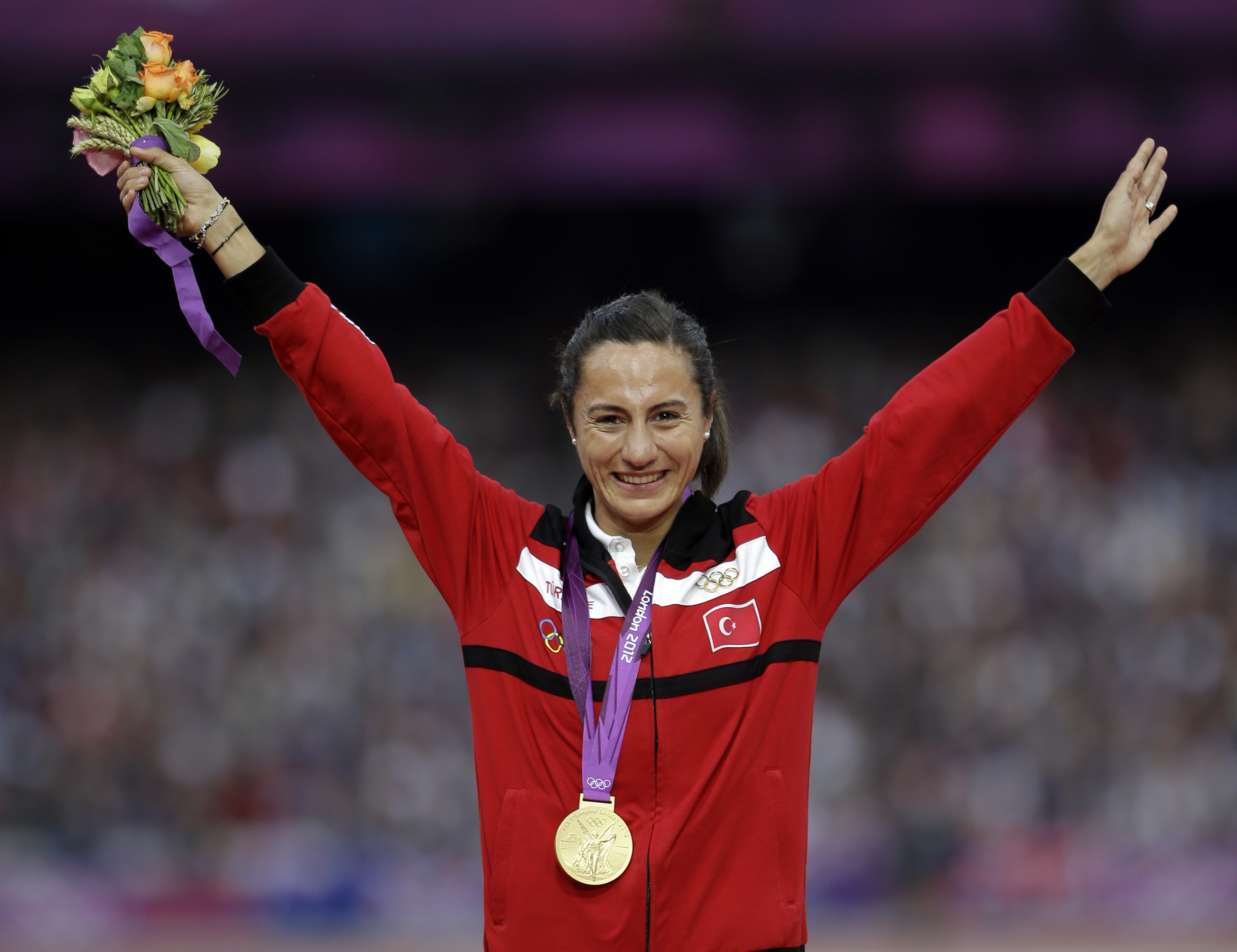 FILE - In this Aug. 11, 2012 file photo Turkey's Asli Cakir Alptekin poses with her gold medal for the women's 1500-meter during the athletics in the Olympic Stadium at the 2012 Summer Olympics, London. Olympic 1,500 meters champion Asli Cakir Alptekin of