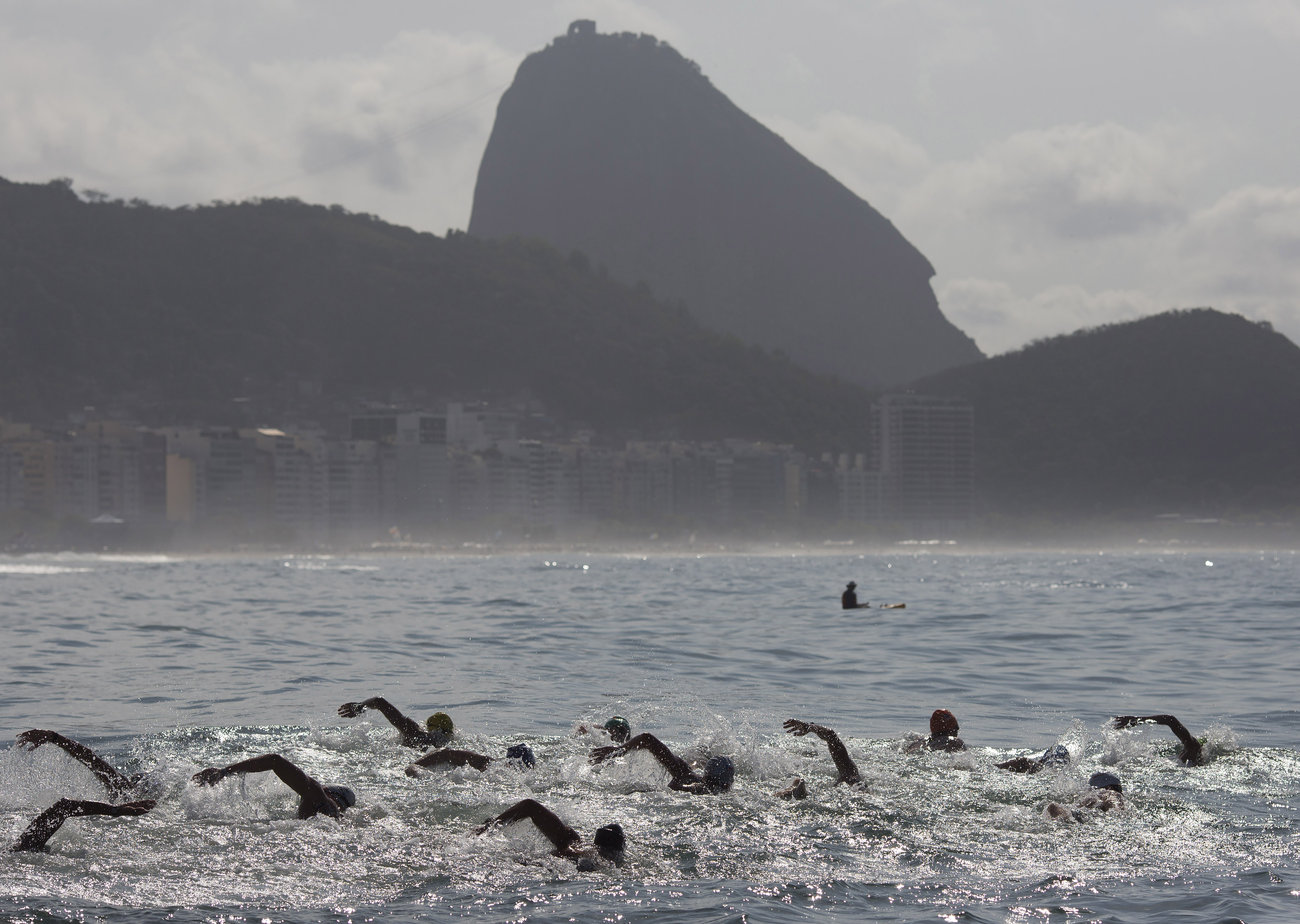 FILE -In this Aug. 22, 2015 file photo, backdropped by Sugar Loaf Mountain, athletes compete in the men's marathon swimming test event, ahead of the Rio 2016 Olympic Games, off Copacabana Beach, Rio de Janeiro, Brazil. Rio's sewage-filled waters are more