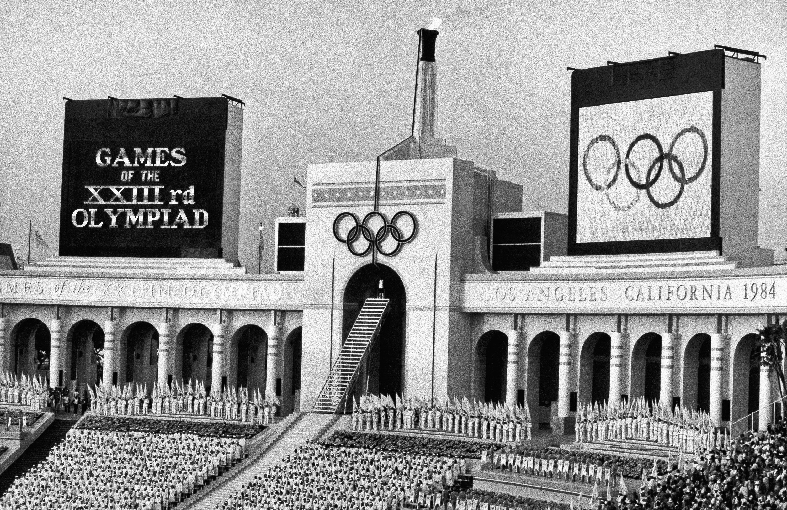 FILE - In this July 28, 1984 file photo, the Olympic flame is flanked by a scoreboard signifying the formal opening of the XXIII Olympiad after it was lit by Rafer Johnson during the opening ceremonies in the Los Angeles Memorial Coliseum. The U.S. Olympi