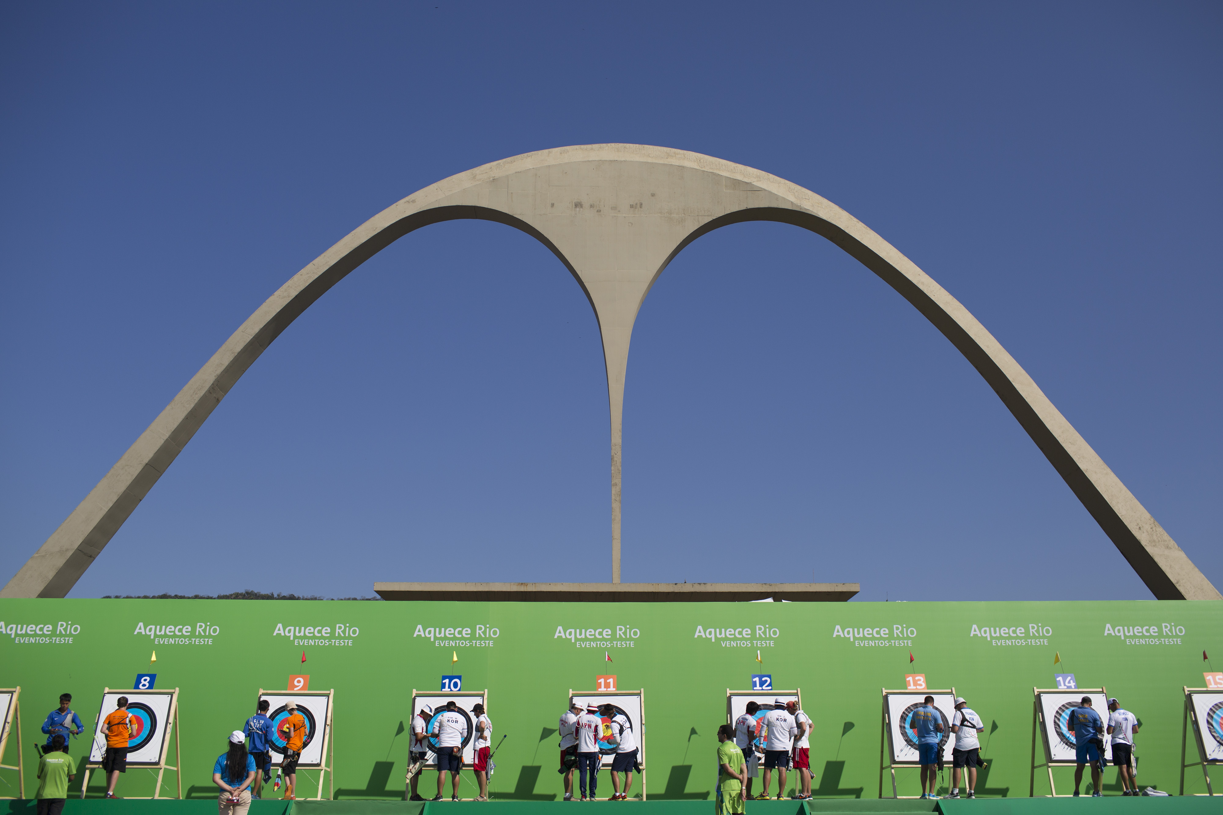 In this Tuesday, Sept. 15, 2015 photo, archers check the targets during the first day of the archery test event for the Rio 2016 Olympic Games at the Sambadrome in Rio de Janeiro, Brazil. Rio's Olympics next year should be a tour guide's delight with many
