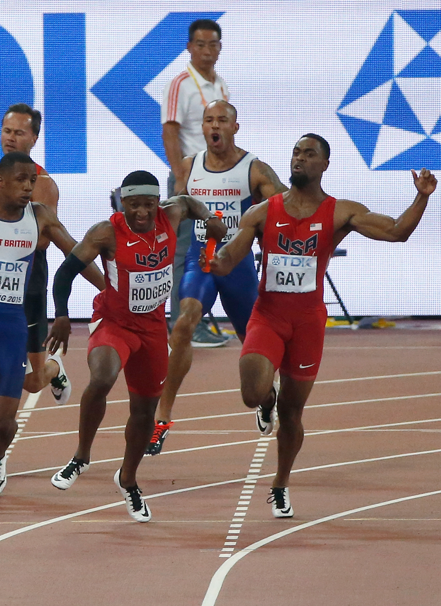 FILE - In this Aug. 29, 2015, file photo, United States' Mike Rodgers, center, takes the baton from Tyson Gay, right, outside of the designated handover zone in the men's 4x100m relay final at the World Athletics Championships at the Bird's Nest stadium i