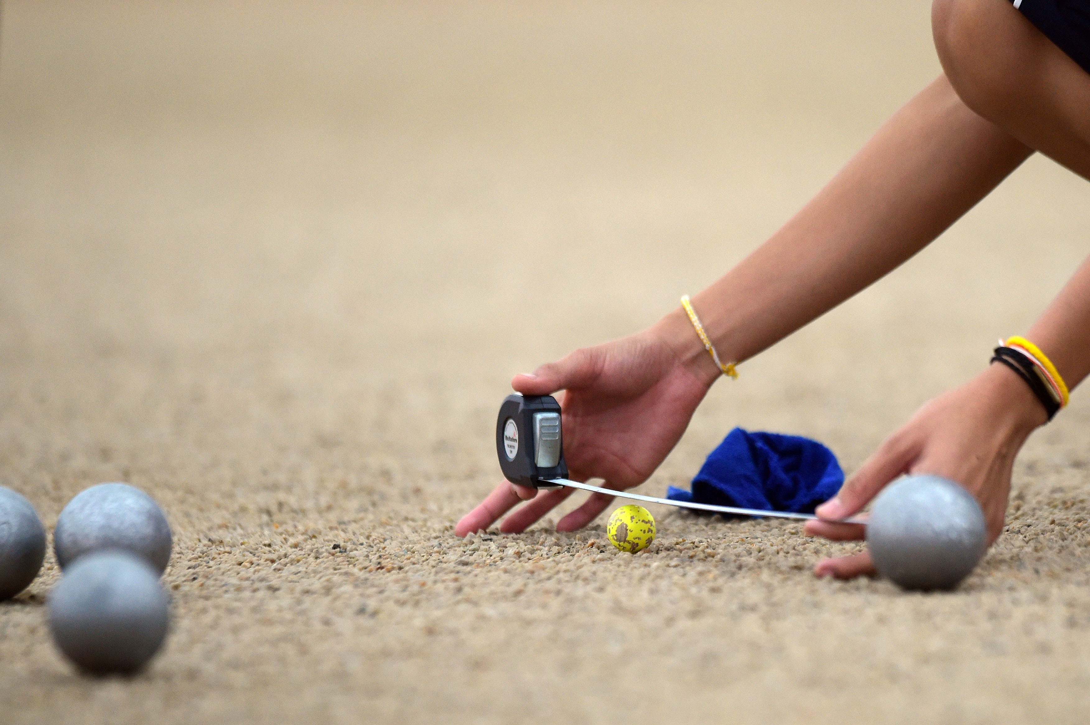 FILE - This Monday, June 8, 2015 file photo shows Bovilak Thepphakan of Laos measuring the distance between the cochonnet and a boule in the Woman's Petanque Singles semifinal match at the SEA Games in Singapore. The sport of boules has launched its bid t