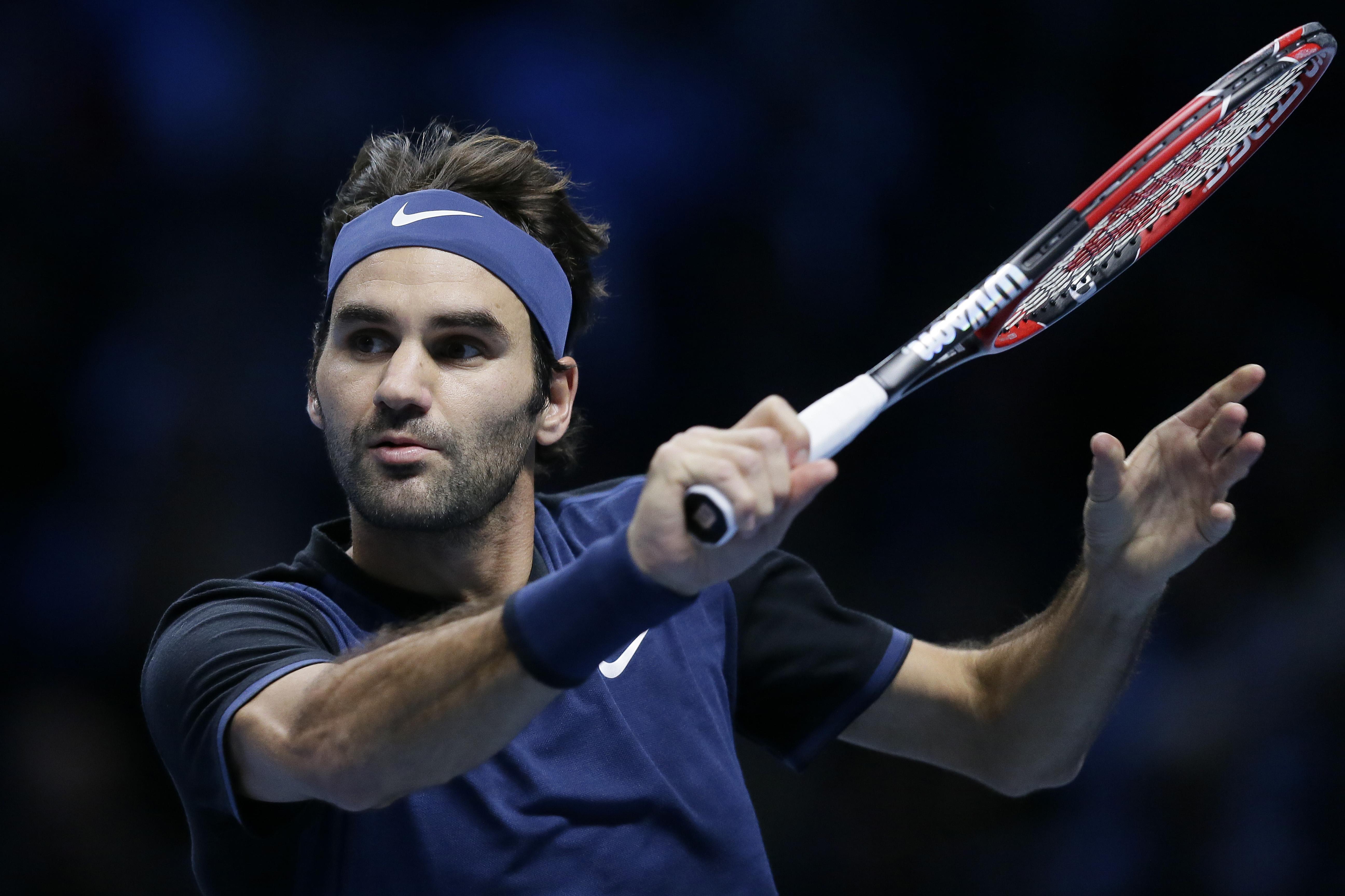 Switzerland's Roger Federer plays a return to Switzerland's Stan Wawrinka during their ATP World Tour Finals semifinal tennis match at the O2 Arena in London, Saturday Nov. 21, 2015. (AP Photo/Tim Ireland)