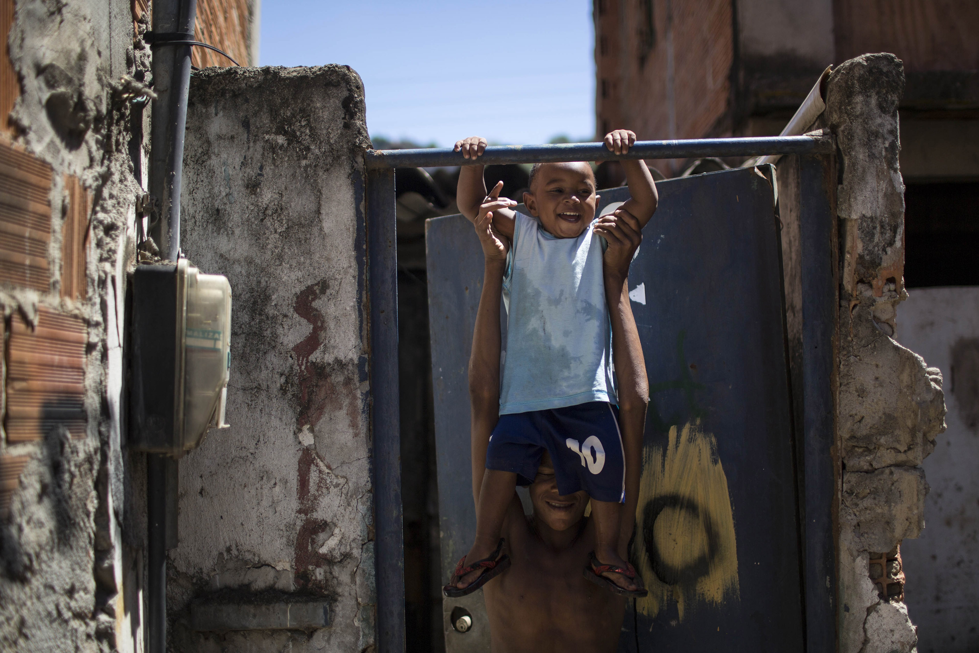 FILE - In this Jan. 10, 2014 file photo, a man plays with a toddler inside the Favela do Metro slum near the Maracana stadium where people have been evicted and homes demolished in preparation for the World Cup and Olympics in Rio de Janeiro, Brazil. A 19