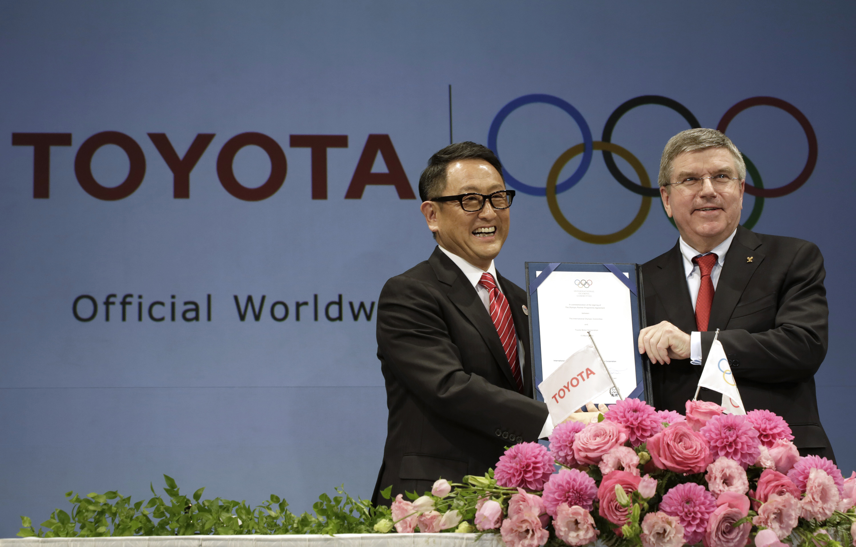 FILE - In this March 13, 2015 file photo, Toyota President and CEO Akio Toyoda, left, smiles with International Olympic Committee (IOC) President Thomas Bach as they pose with a signed document during a press conference in Tokyo as the Japanese auto giant