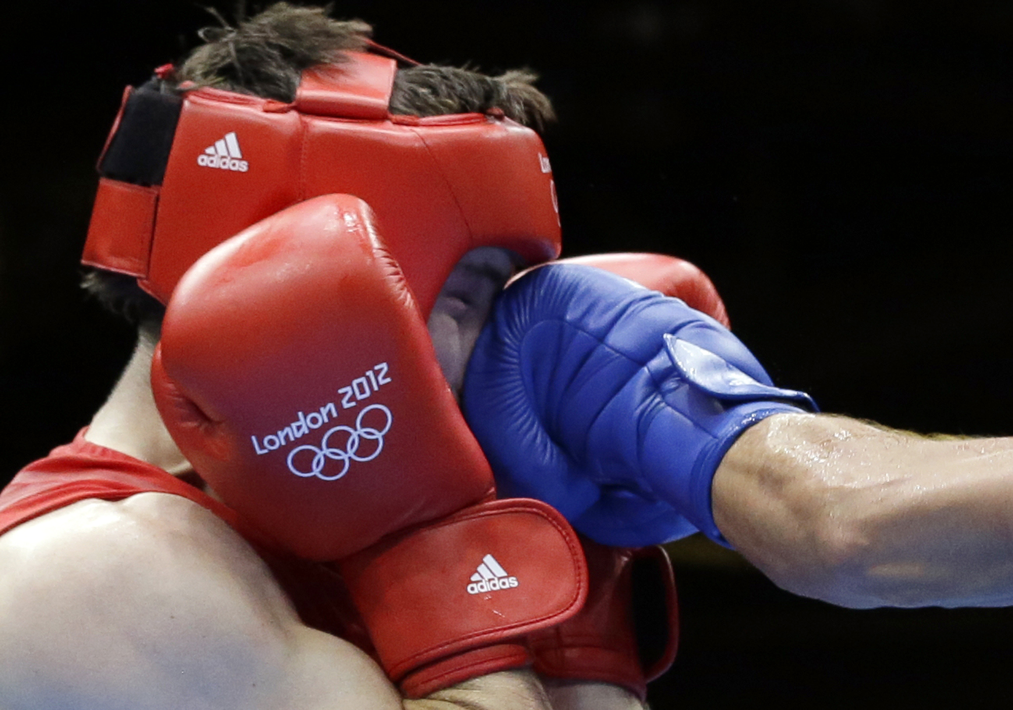 FILE- In this Aug. 12, 2012, file photo, Britain's Freddie Evans is hit by a punch from Kazakhstan's Serik Sapiyev during a welterweight 69-kg gold medal boxing match at the 2012 Summer Olympics in London. Male boxers won't be wearing protective headgear