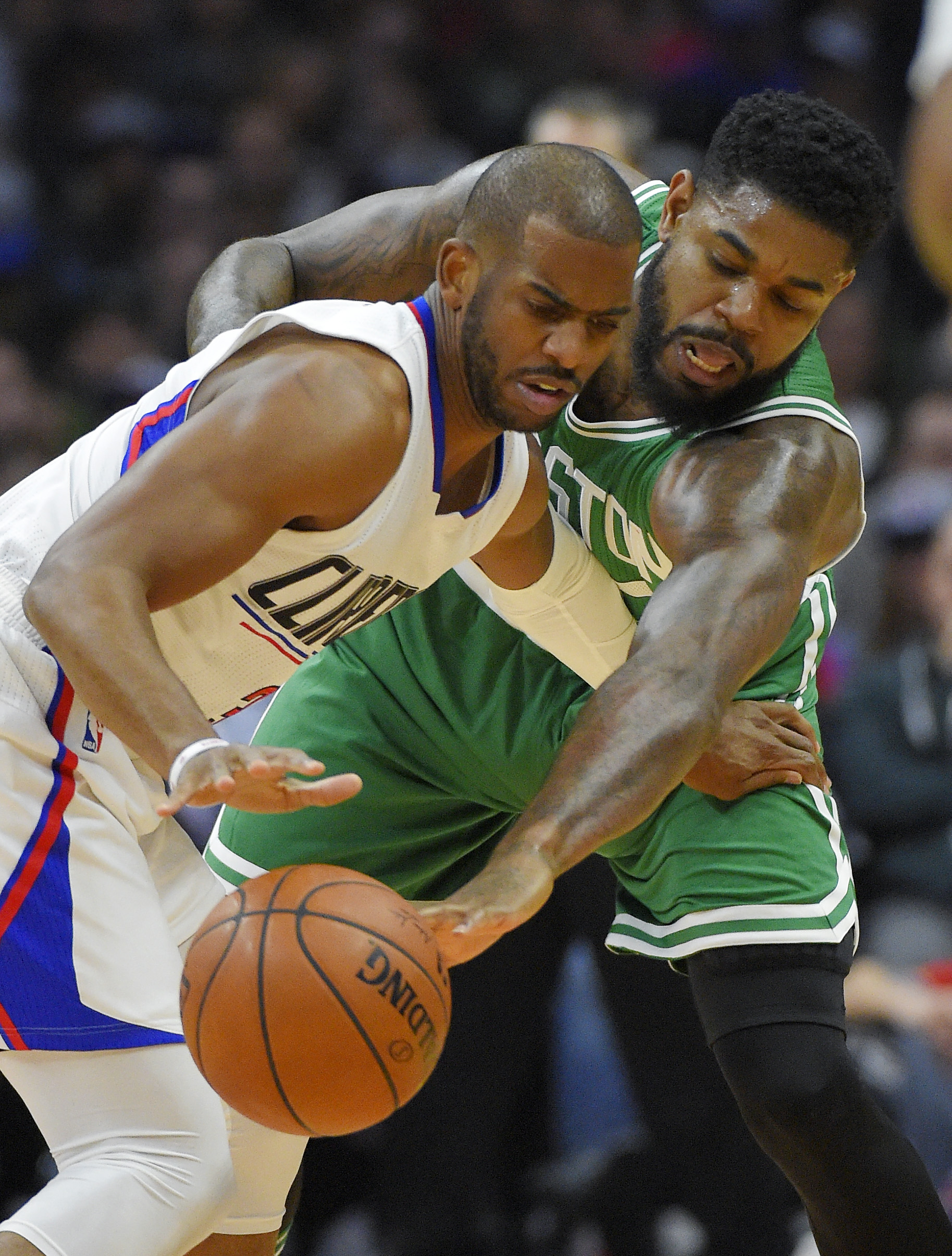 Boston Celtics guard Avery Bradley, right, reaches in on Los Angeles Clippers guard Chris Paul,left, during the first half of an NBA basketball game, Monday, March 28, 2016, in Los Angeles. (AP Photo/Mark J. Terrill)