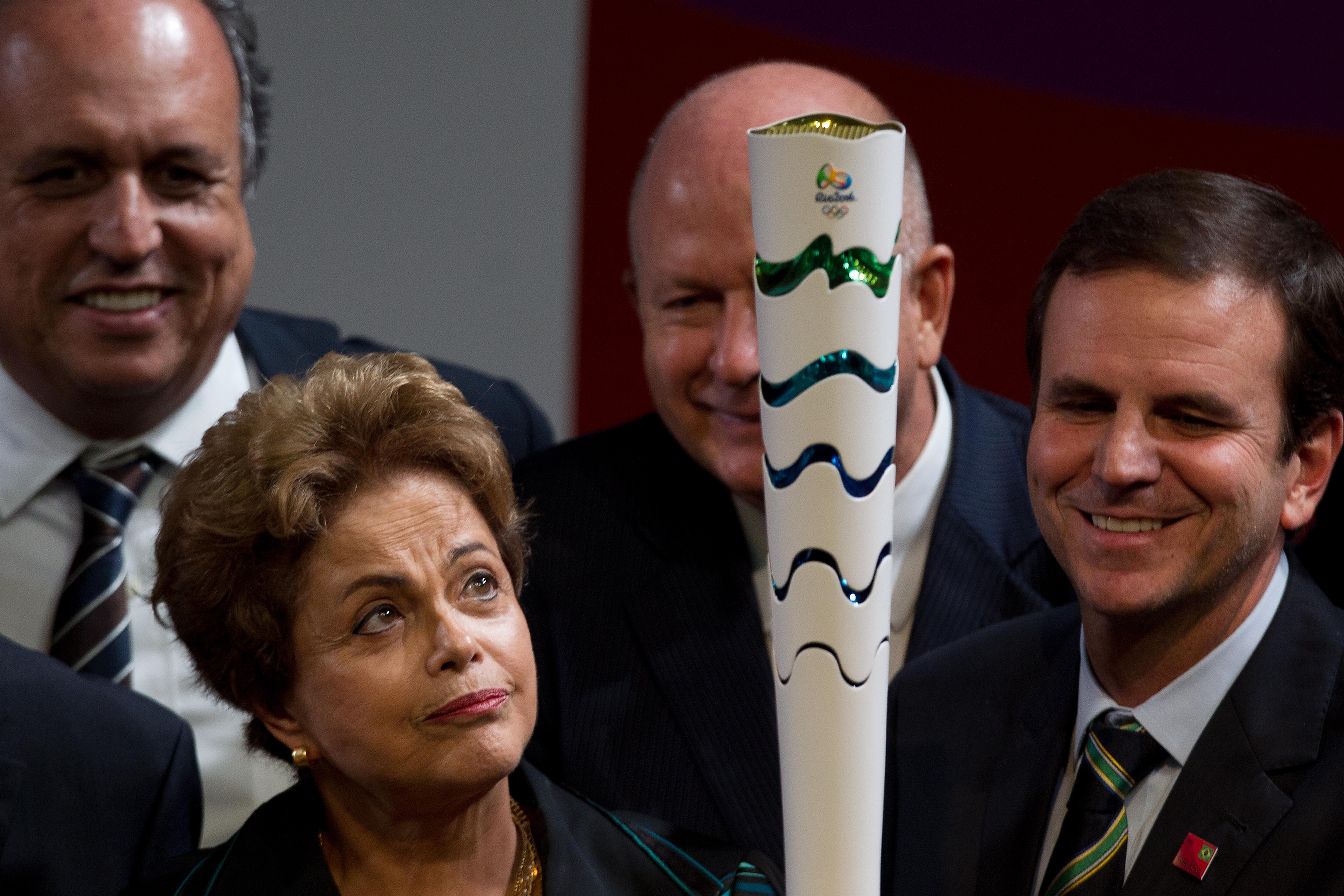 FILE -  In this July 3, 2015 photo, Brazil's President Dilma Rousseff, left, and Rio de Janeiro Mayor Eduardo Paes look at the Olympic Torch as it's presented during a ceremony ahead of the 2016 Rio Olympic Games in Brasilia, Brazil. The former head of na