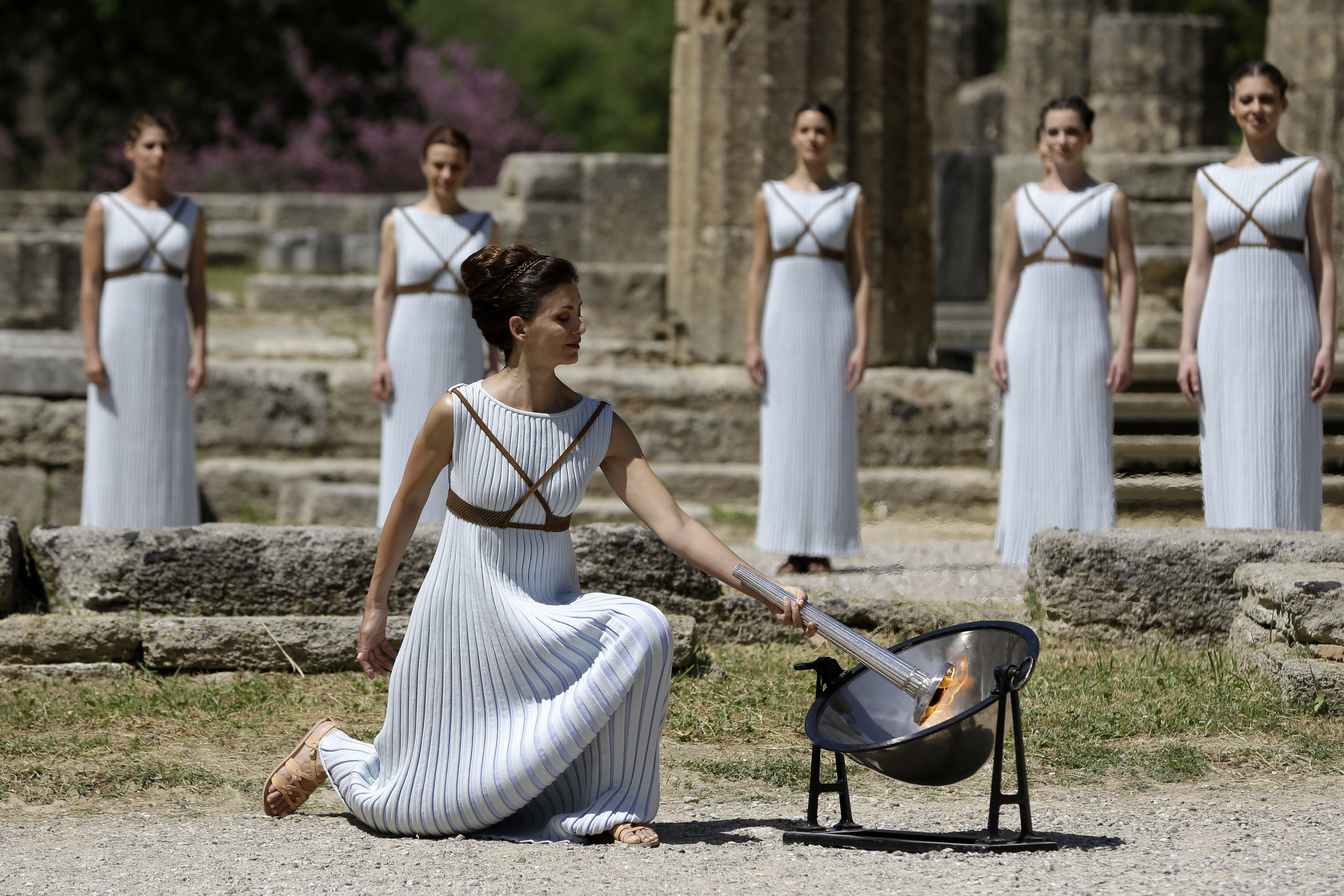 Actress Katerina Lehou, right, as high priestess, lights the Olympic Flame, during the final dress rehearsal of the lighting of the Olympic flame at Ancient Olympia, in western Greece on Wednesday, April 20, 2016. The flame will be transported by torch re