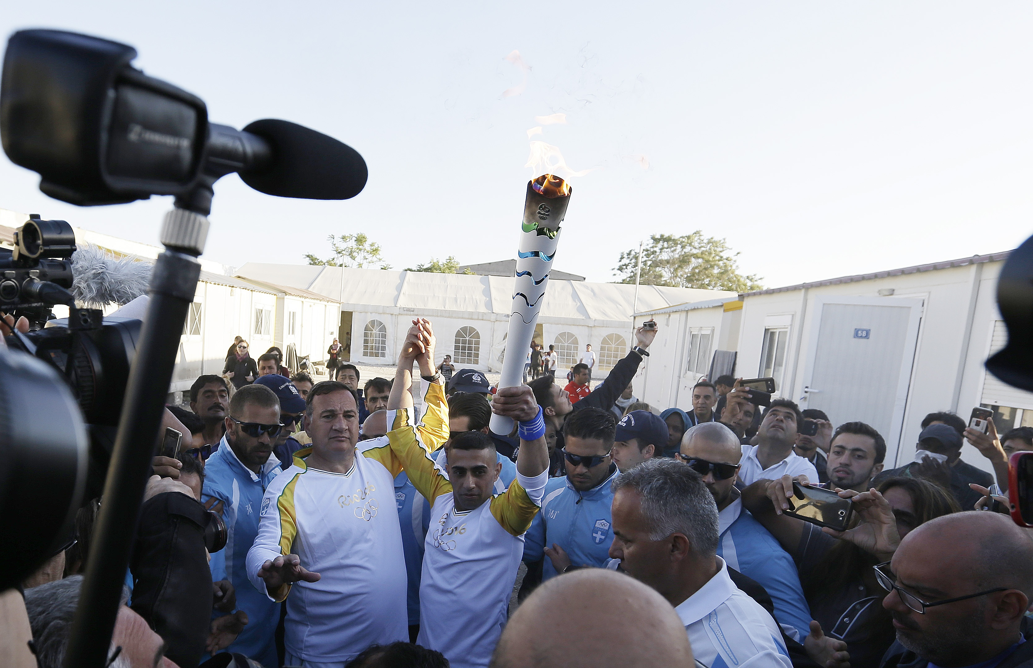 Syrian refugee Ibrahim Al-Hussein, 27, center, freestyle swimmer, basketball player and former judo wrestler holds the Olympic flame as the head of Greece's Olympic Committee, Spyros Capralos, holds his hand at the Elaionas camp that is home to about 1,50