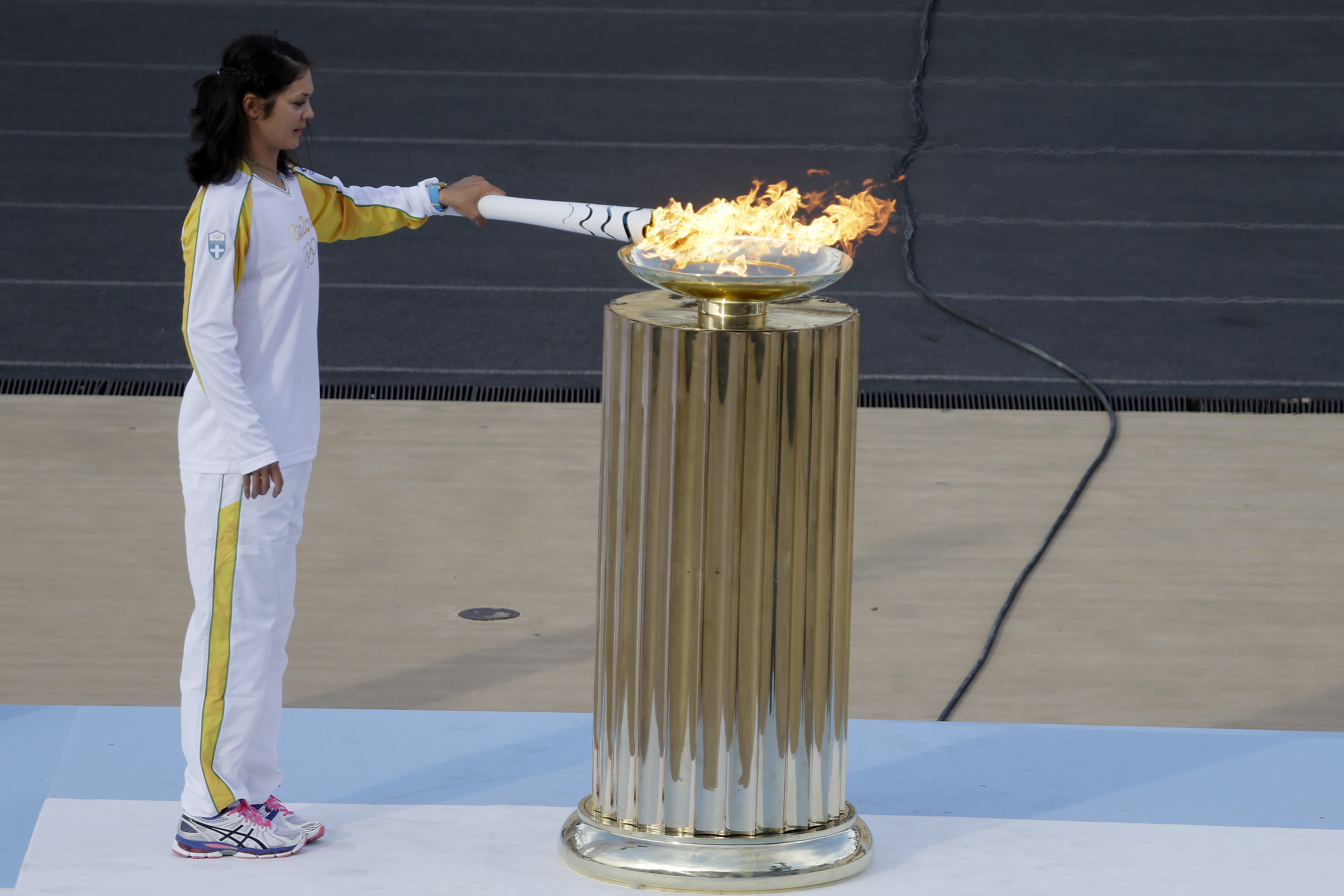 Rowing World Champion Katerina Nikolaidou of Greece lights the cauldron during the handover ceremony for the Olympic Flame at Panathinean stadium in Athens, Wednesday, April 27, 2016. The flame arrives in Brazil on May 3, and will be relayed across the va