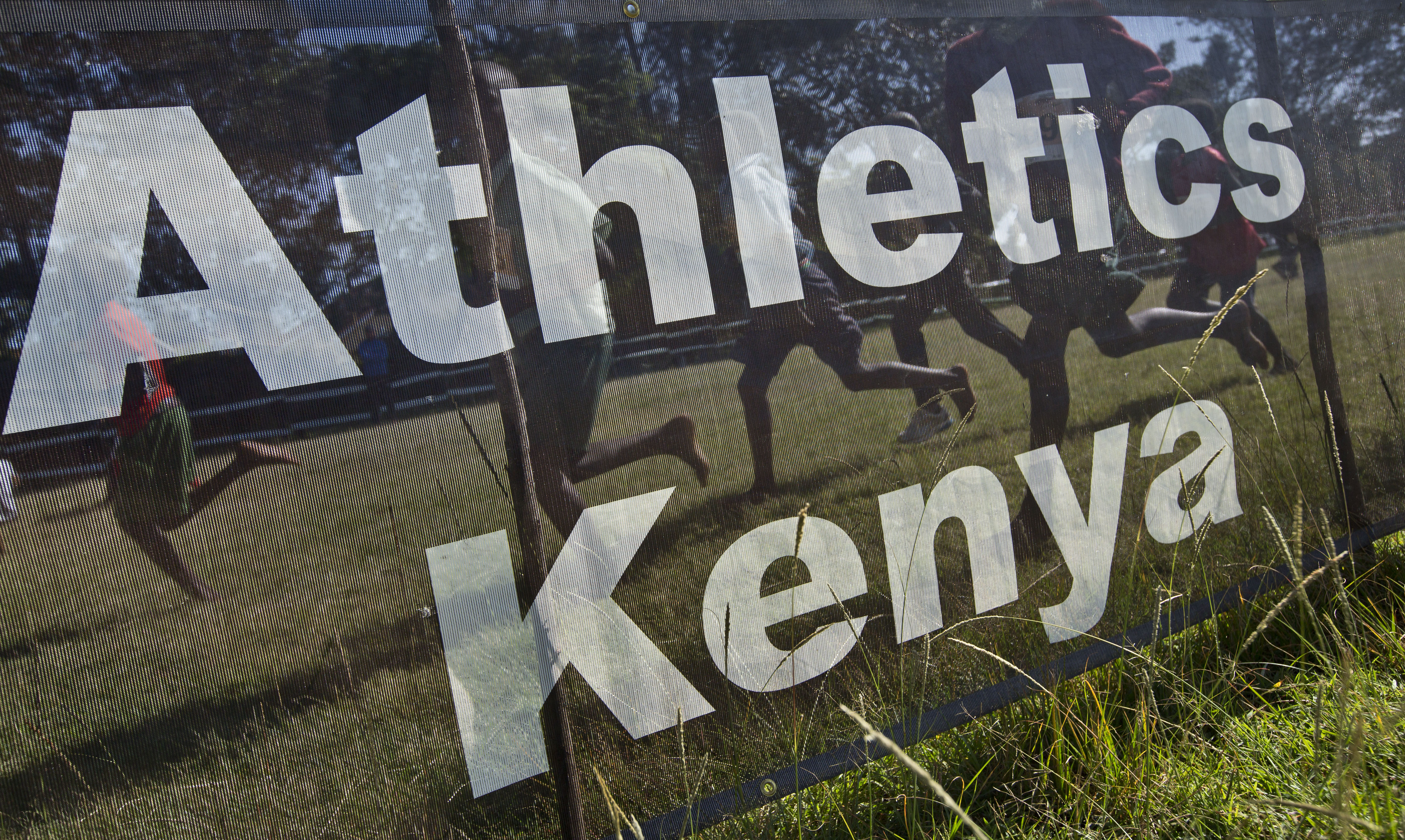 FILE - In this Sunday, Jan. 31, 2016 file photo, junior athletes run past a sign for Athletics Kenya at the Discovery cross country races, an annual race held to identify up-and-coming new young talent, in Eldoret, Kenya. World Anti-Doping Agency (WADA) o