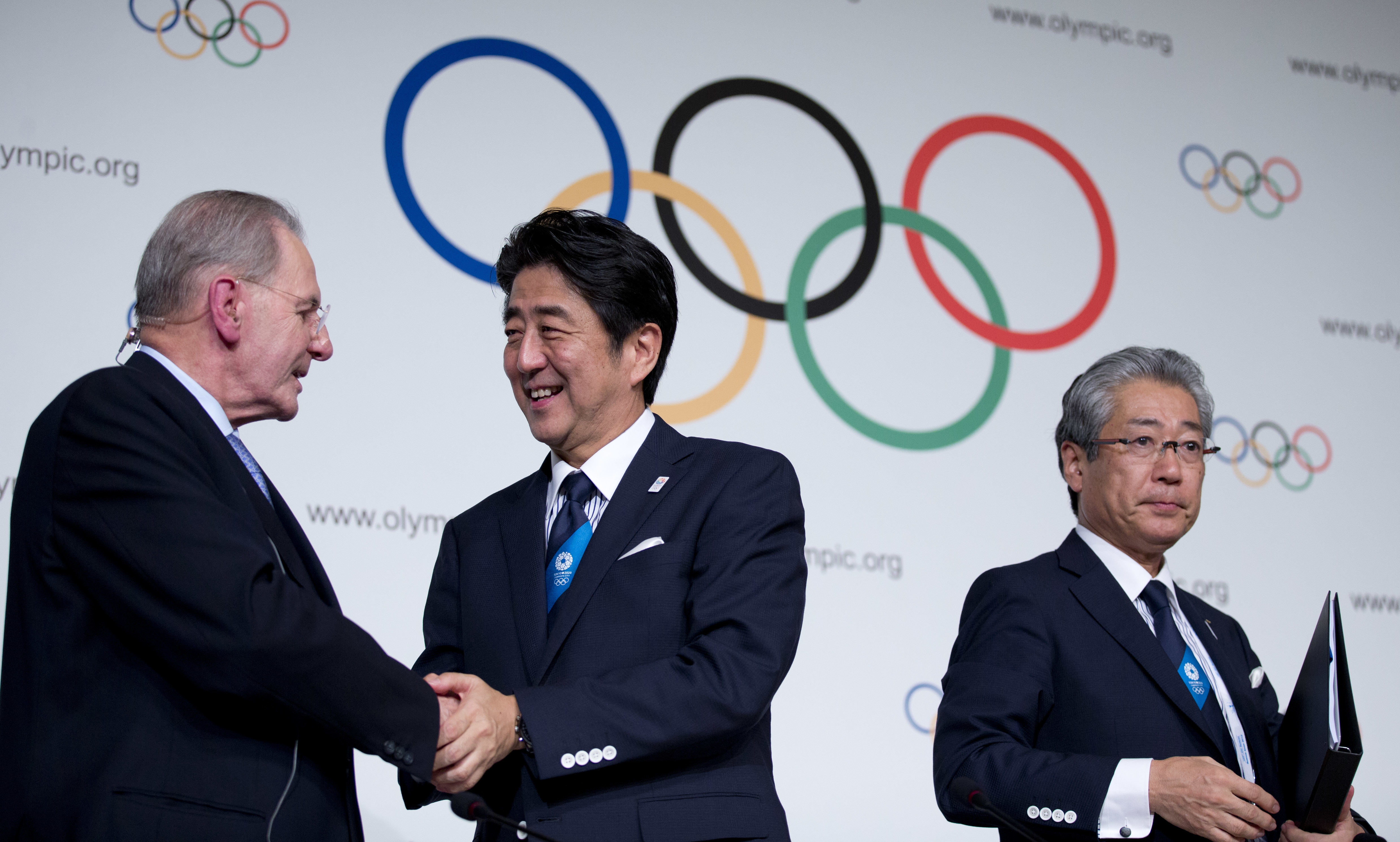 FILE - In this Sept. 7, 2013, file photo, Japan's Prime Minister Shinzo Abe, center, shakes hands with President of the International Olympic Committee Jacques Rogge as Tokyo 2020 Olympic Bid Committee President Tsunekazu Takeda stands by after signing th