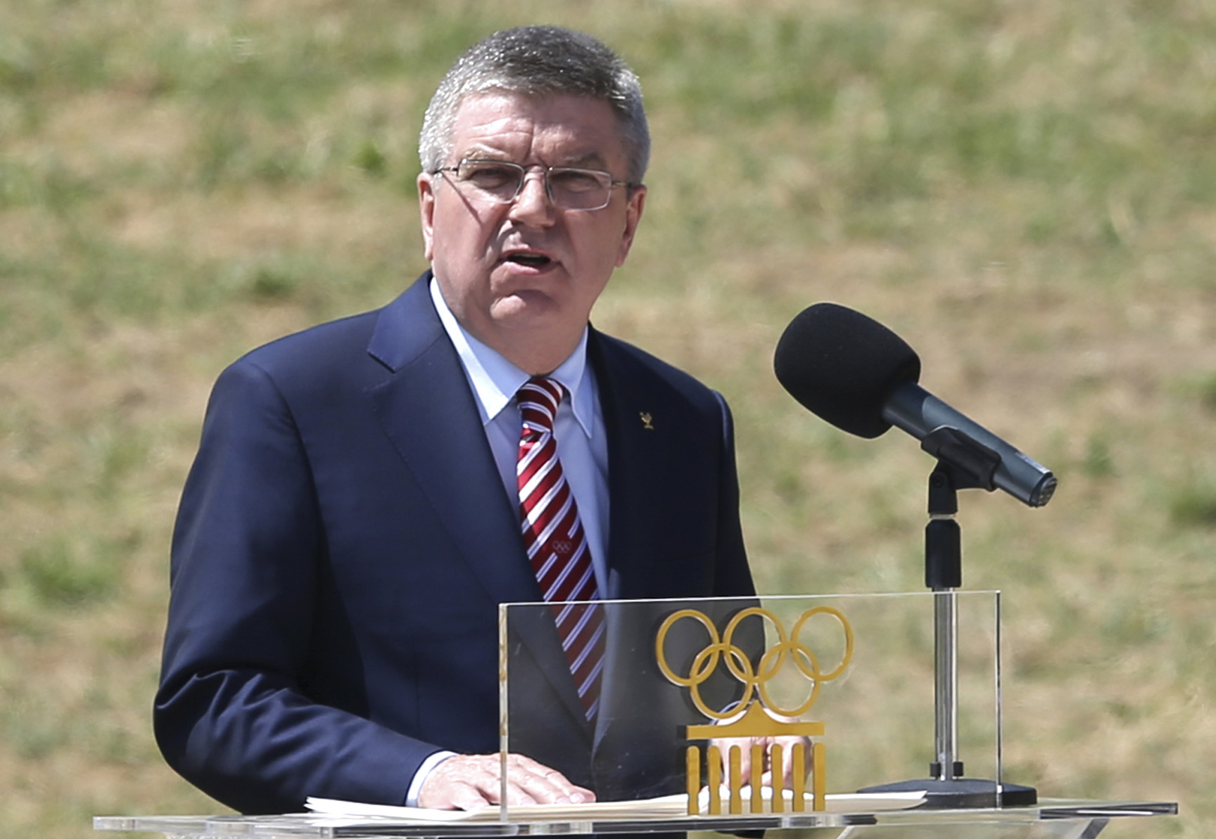 FILE- In this Thursday, April 21, 2016 file photo, IOC President Thomas Bach delivers a speech during the ceremonial lighting of the Olympic flame in Ancient Olympia, Greece. Bach says entire sports federations could be suspended if allegations of state-s