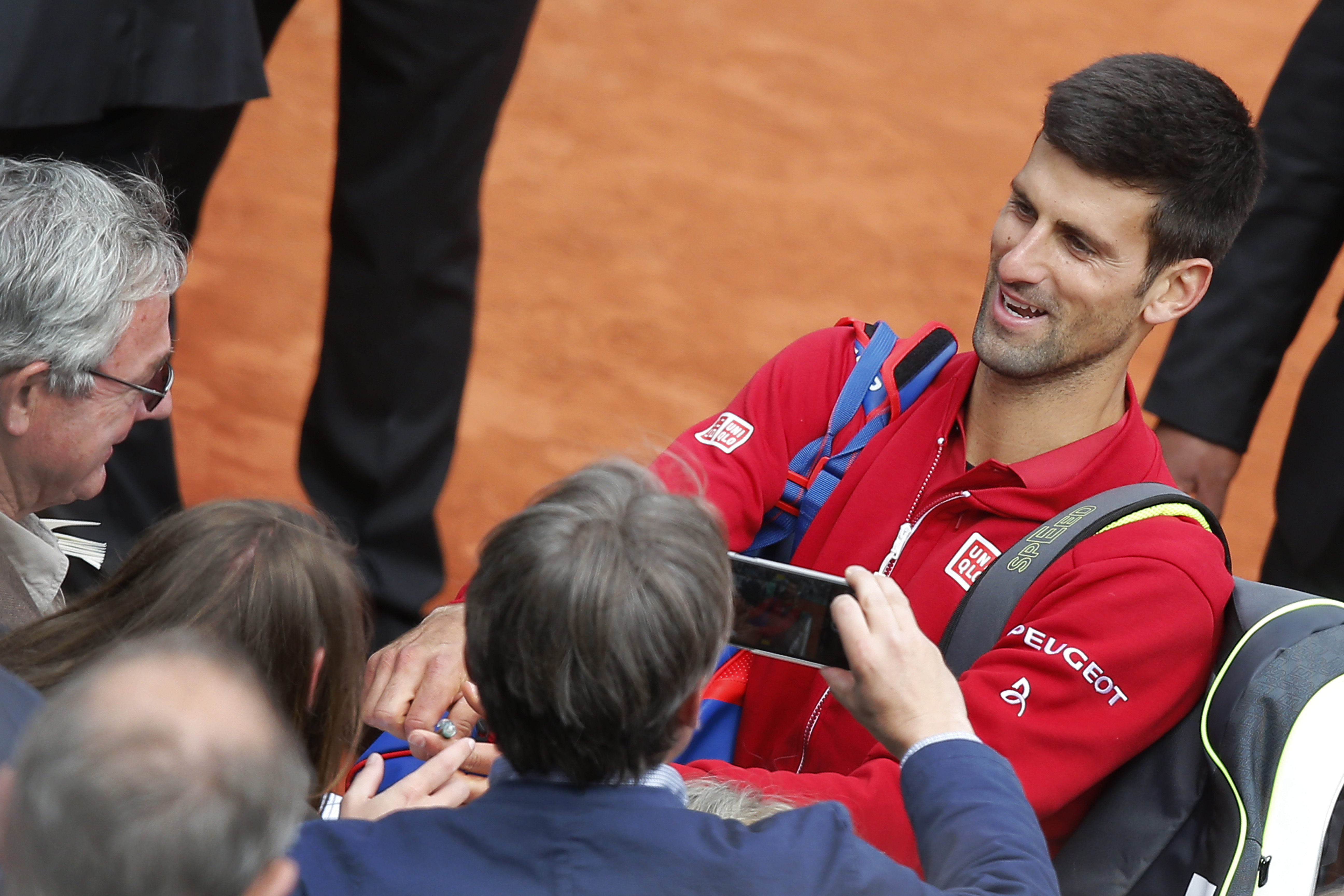 Serbia's Novak Djokovic signs autographs after winning his first round match of the French Open tennis tournament against Yen-Hsun Lu of Taiwan at the Roland Garros stadium in Paris, France, Tuesday, May 24, 2016. (AP Photo/Michel Euler)