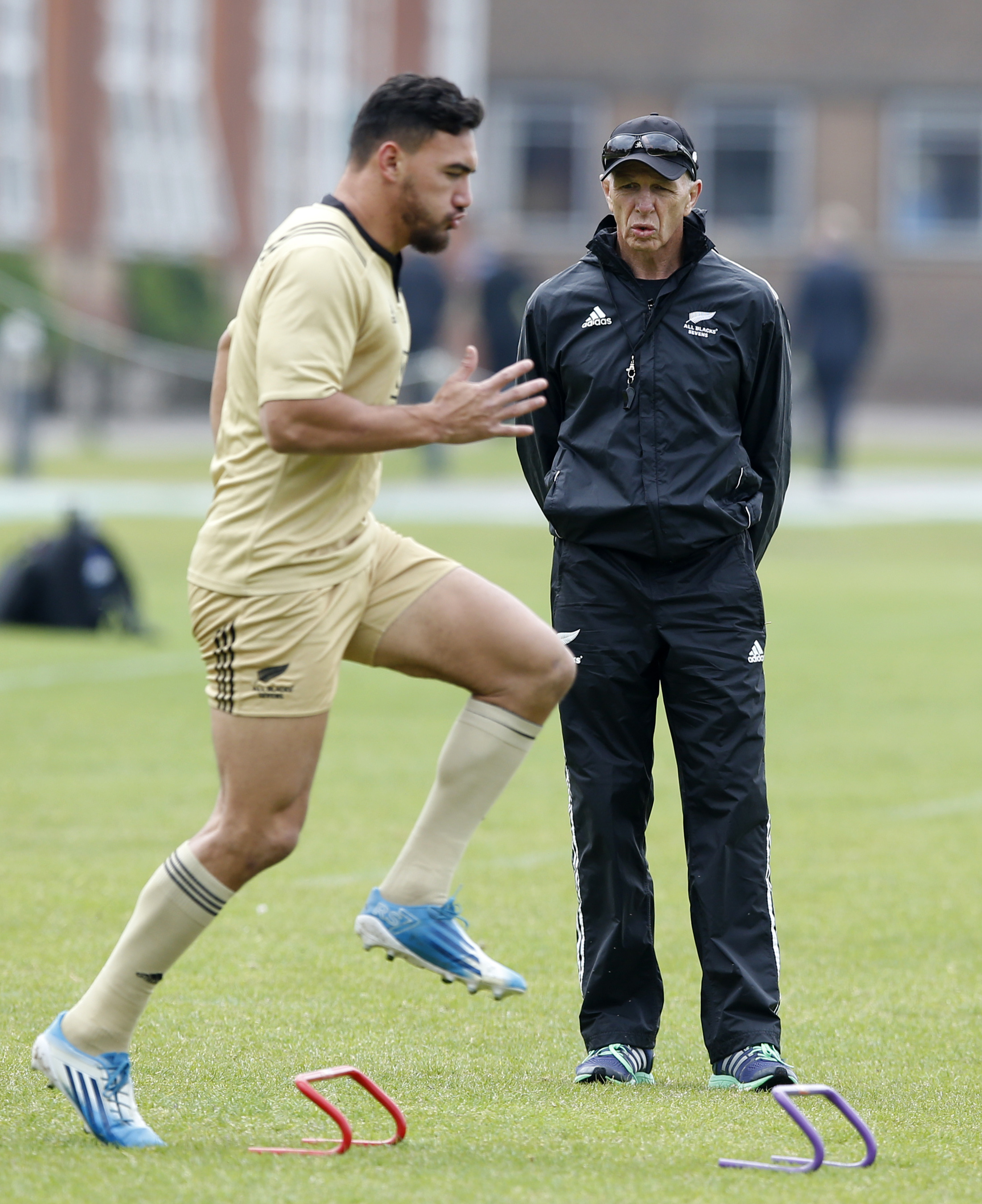 In this photo taken Thursday May 19, 2016, Gordon Tietjens, left, the New Zealand rugby 7's coach, watches his players train at Dulwich College in London. The mere length of Tietjens' tenure as New Zealand's rugby sevens coach, 22 years and counting, is e