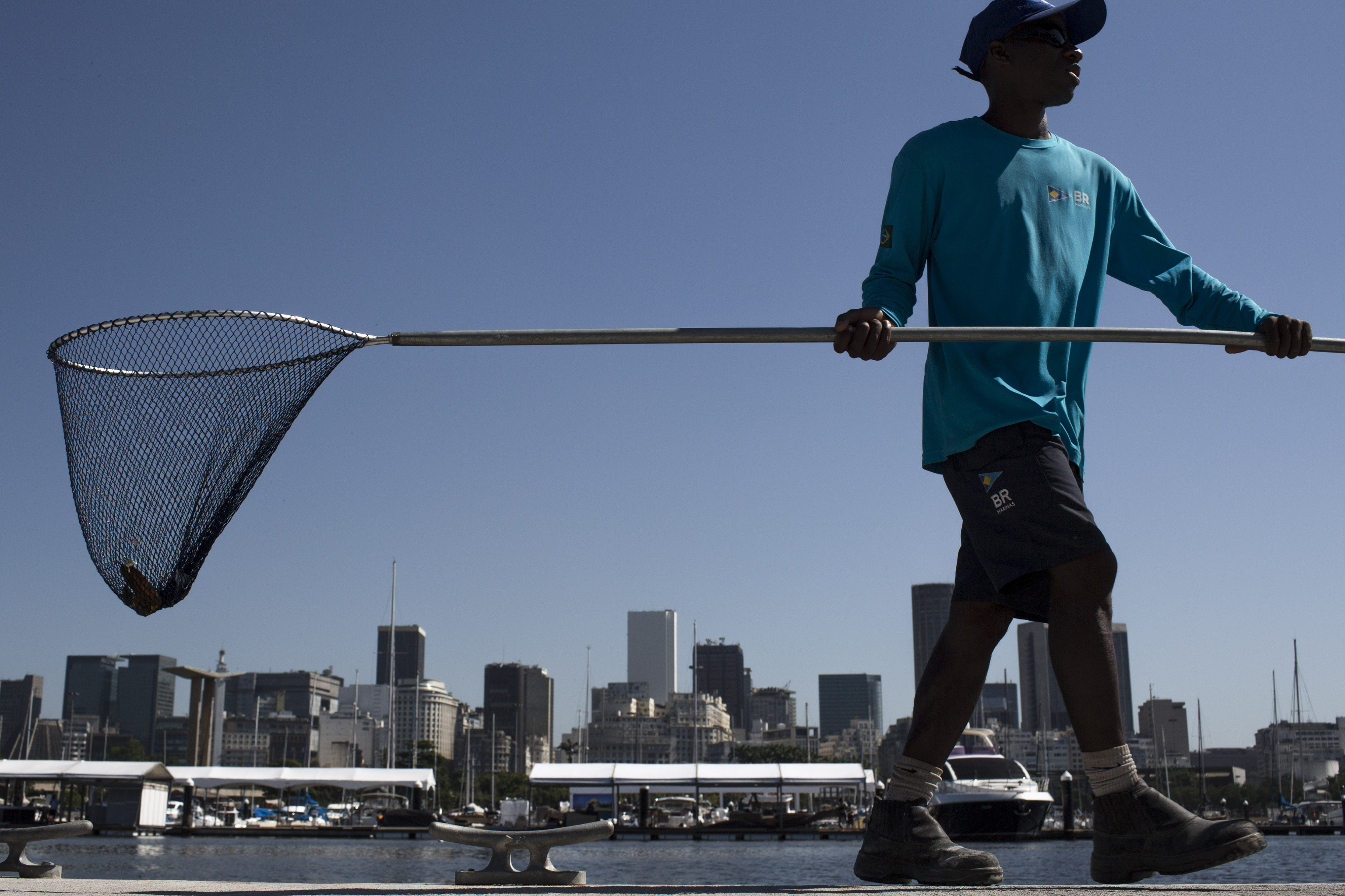 FILE - In this April 7, 2016 file photo, a worker collects floating trash from Guanabara Bay during the inauguration of the renovated Marina da Gloria in Rio de Janeiro, Brazil. Andy Hunt, the head of World Sailing, met with city, state, and organizing co