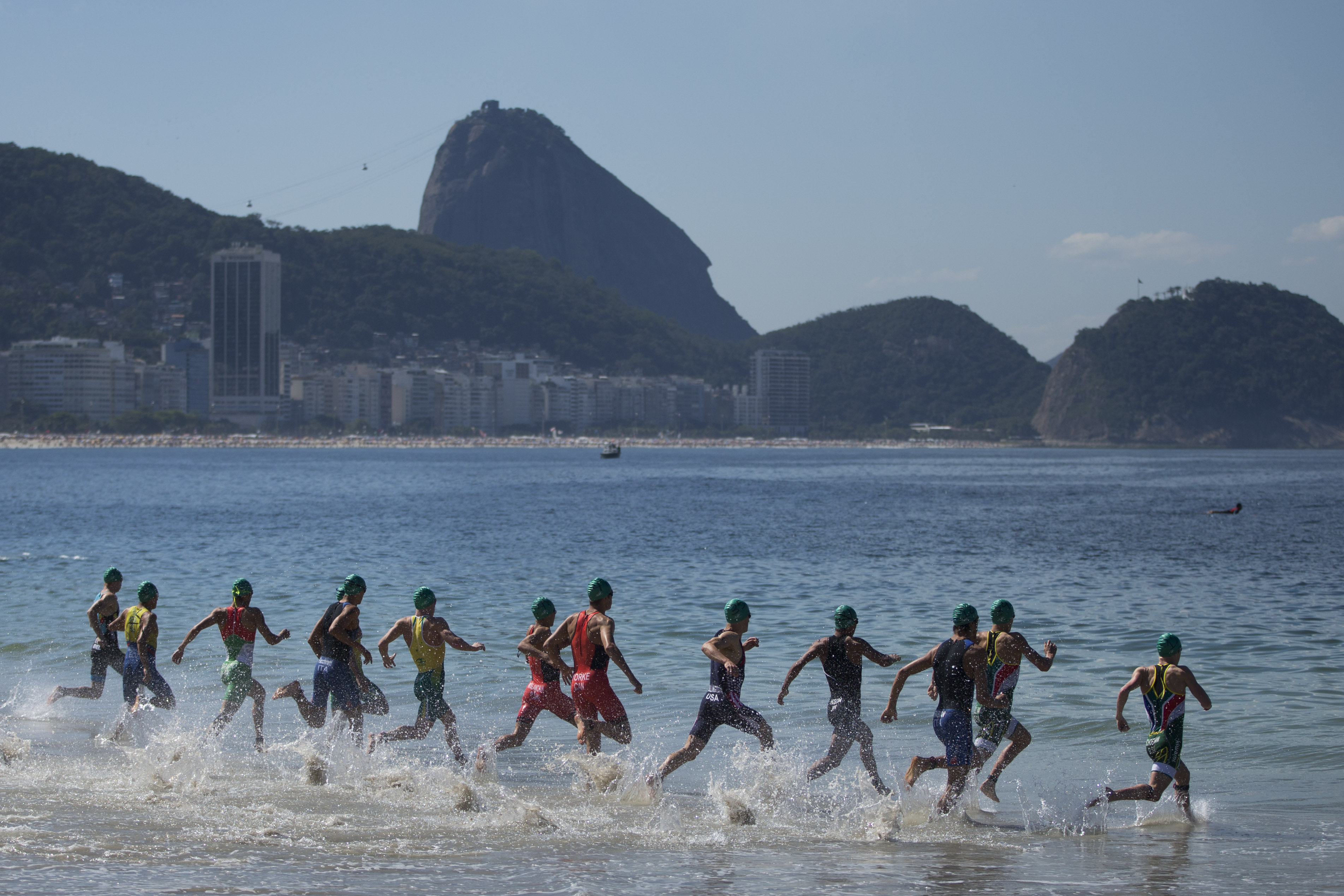 FILE - In this Aug. 2, 2015, file photo, triathletes enter the water at the start of the men's triathlon ITU World Olympic Qualification Event in Rio de Janeiro, Brazil. Hundreds of thousands of foreign visitors are expected for the Olympics, which open A
