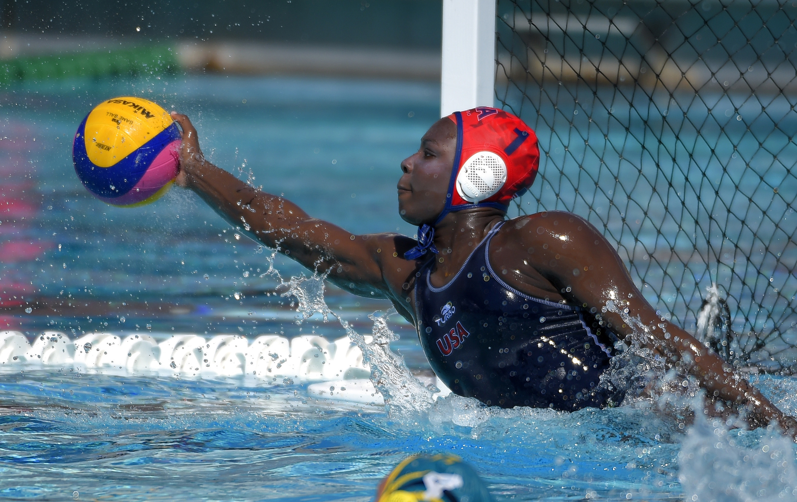 In this May 22, 2016, photo, U.S. goalkeeper Ashleigh Johnson stops a shot during an exhibition water polo match against Australia in Los Angeles. Johnson, a goaltender blessed with jaw-dropping athleticism, is a lock for Rio de Janeiro, putting her on tr