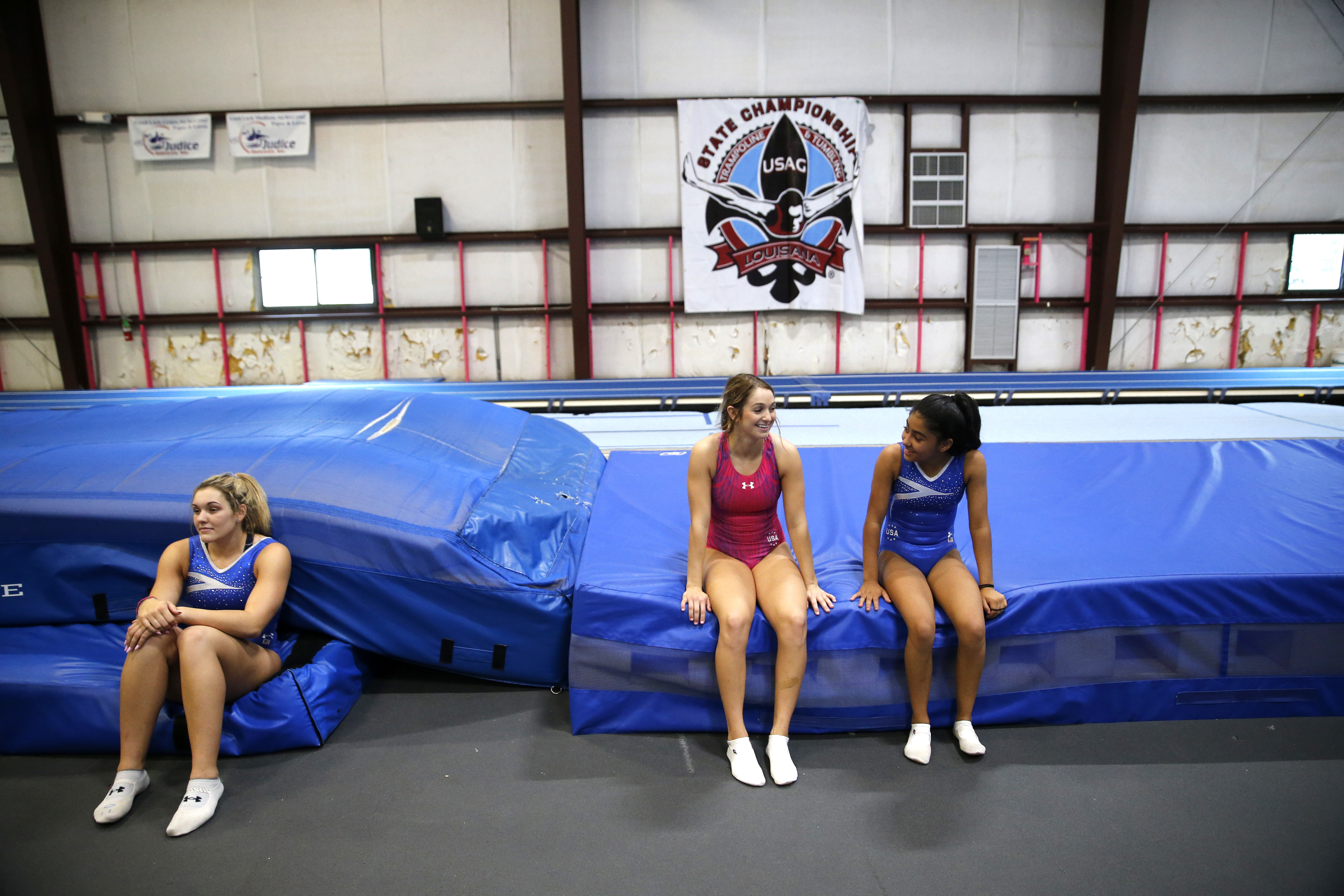 Dakota Earnest, left, Shaylee Dunavin and Ellen Heinen, right, take a break during practice in Lafayette, La., Wednesday, May 25, 2016. They are training for trials that begin June 11 in Providence, R.I., which will decide which man and woman will represe