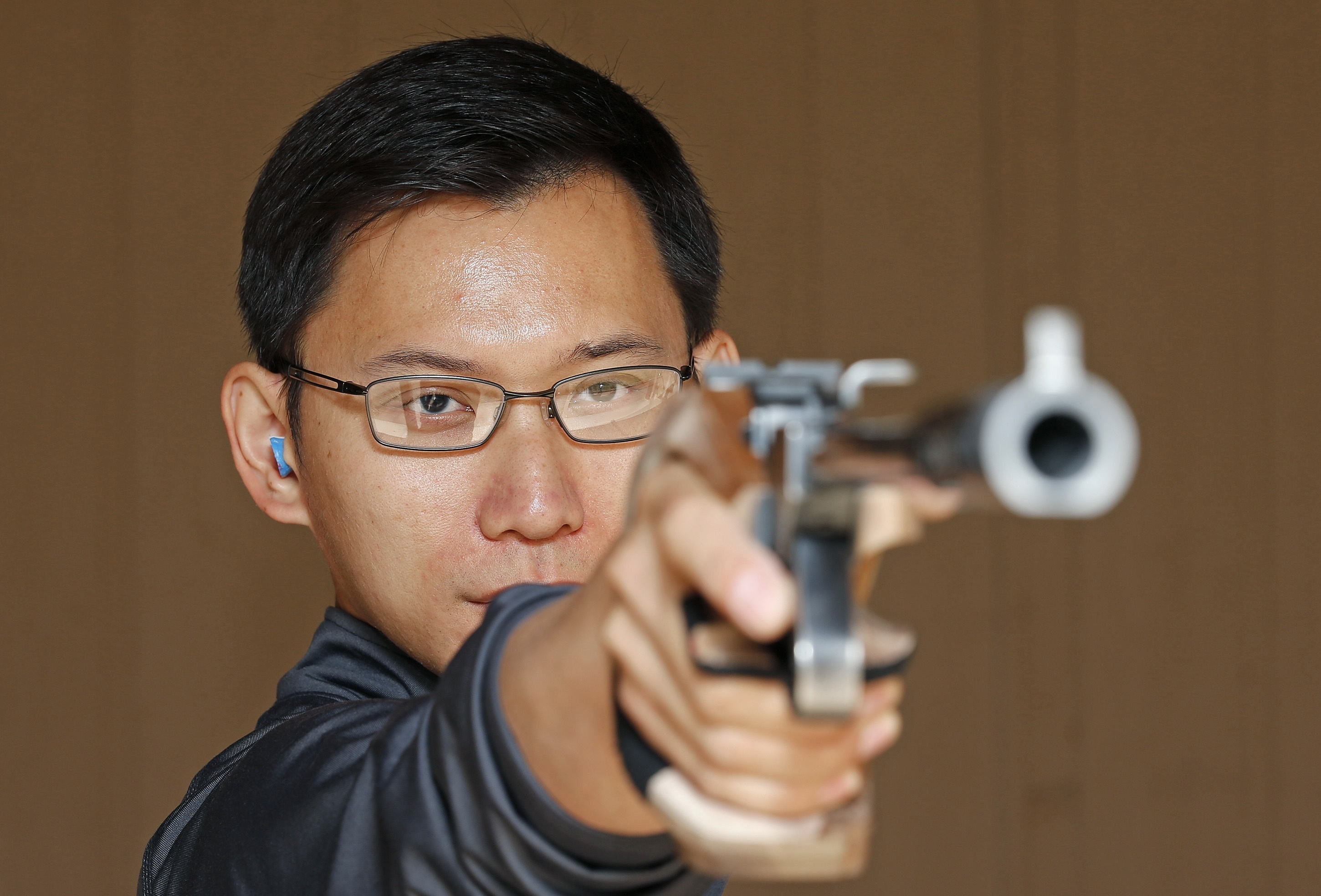 In this photo taken, Saturday, May 7, 2016, Jay Shi, an Olympics qualifier for the 2016 Rio Olympics in free pistol and air pistol, practices at a local shooting range in Phoenix. Shi has overcome damaged to his right eye to qualify for U.S. Olympic Team.