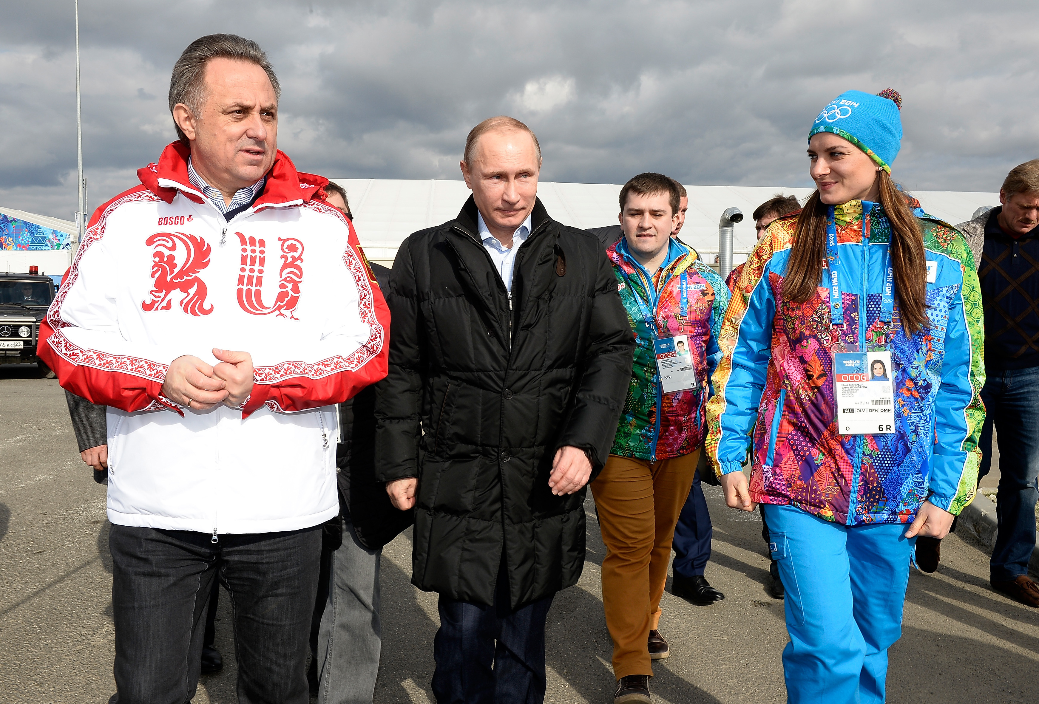 FILE - In this Feb. 5, 2014 file photo Russian Minister of Sport, Tourism and Youth policy Vitaly Mutko, left, Russian President Vladimir Putin, center, and Olympic Village Mayor and Pole Vaulter Yelena Isinbayeva visit the Coastal Cluster Olympic Village