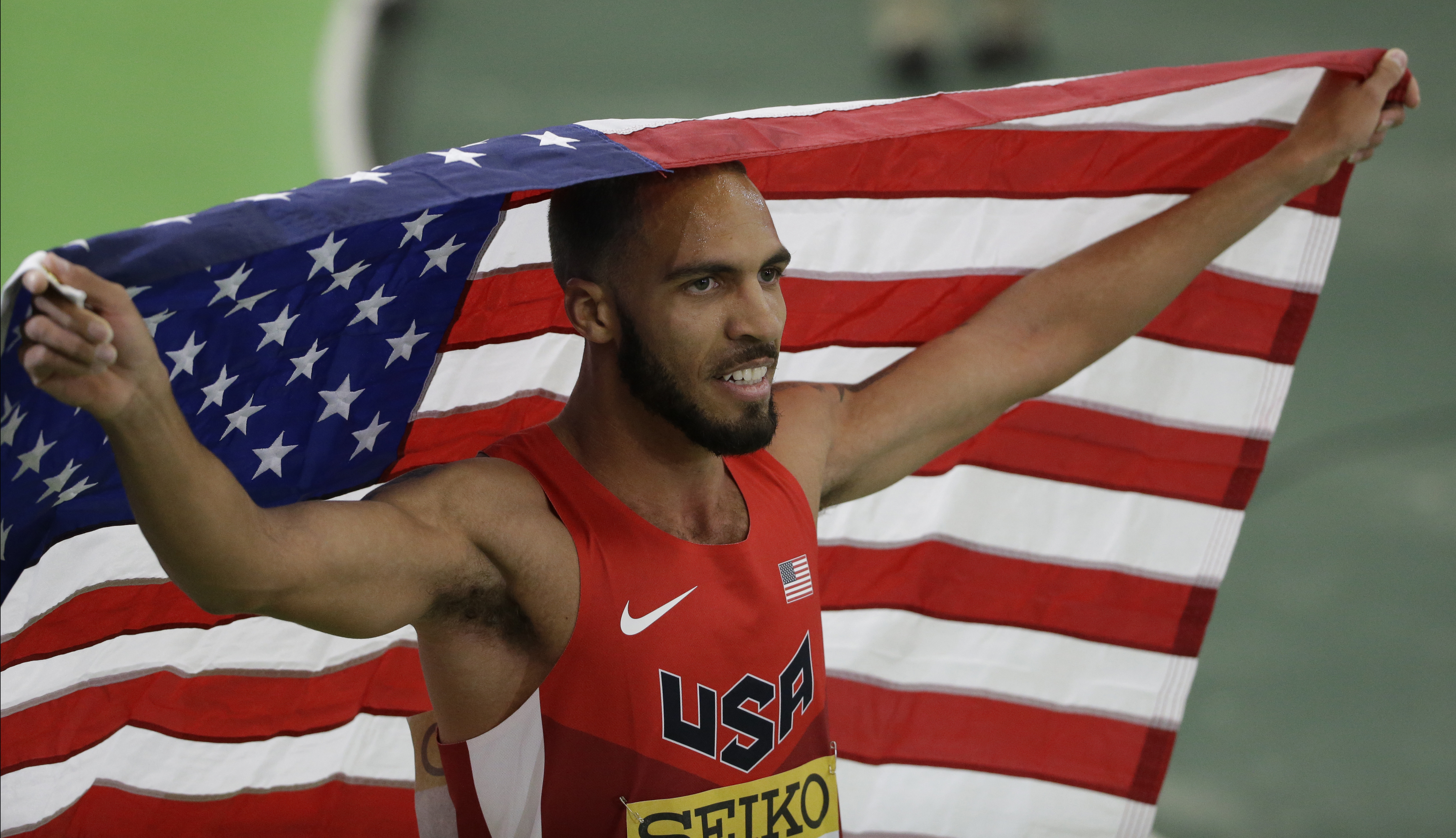 FILE - In this March 19, 2016, file photo, United States' Boris Berian holds the U.S. flag after he won the men's 800-meter sprint final during the World Indoor Athletics Championships, in Portland, Ore.   Nike is dropped its lawsuit against Boris Berian