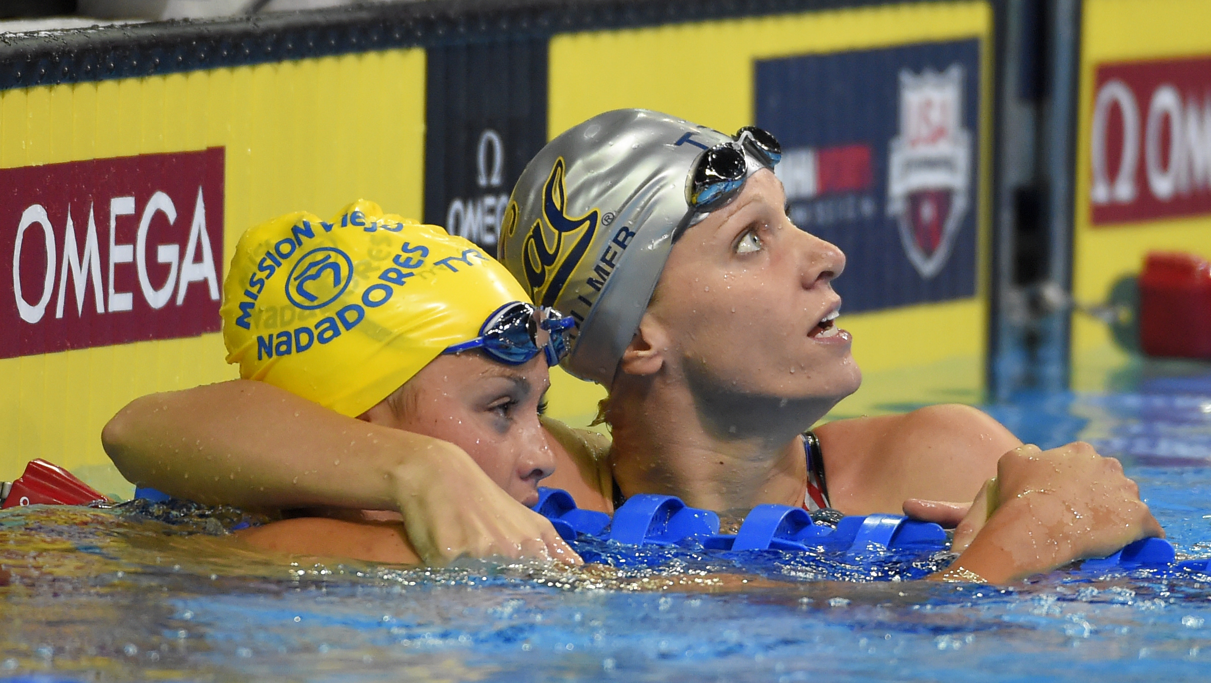 Dana Vollmer hugs Katie McLaughlin, left, as she checks her time after a women's 100-meter butterfly semifinal at the U.S. Olympic swimming trials, Sunday, June 26, 2016, in Omaha, Neb. (AP Photo/Mark J. Terrill)