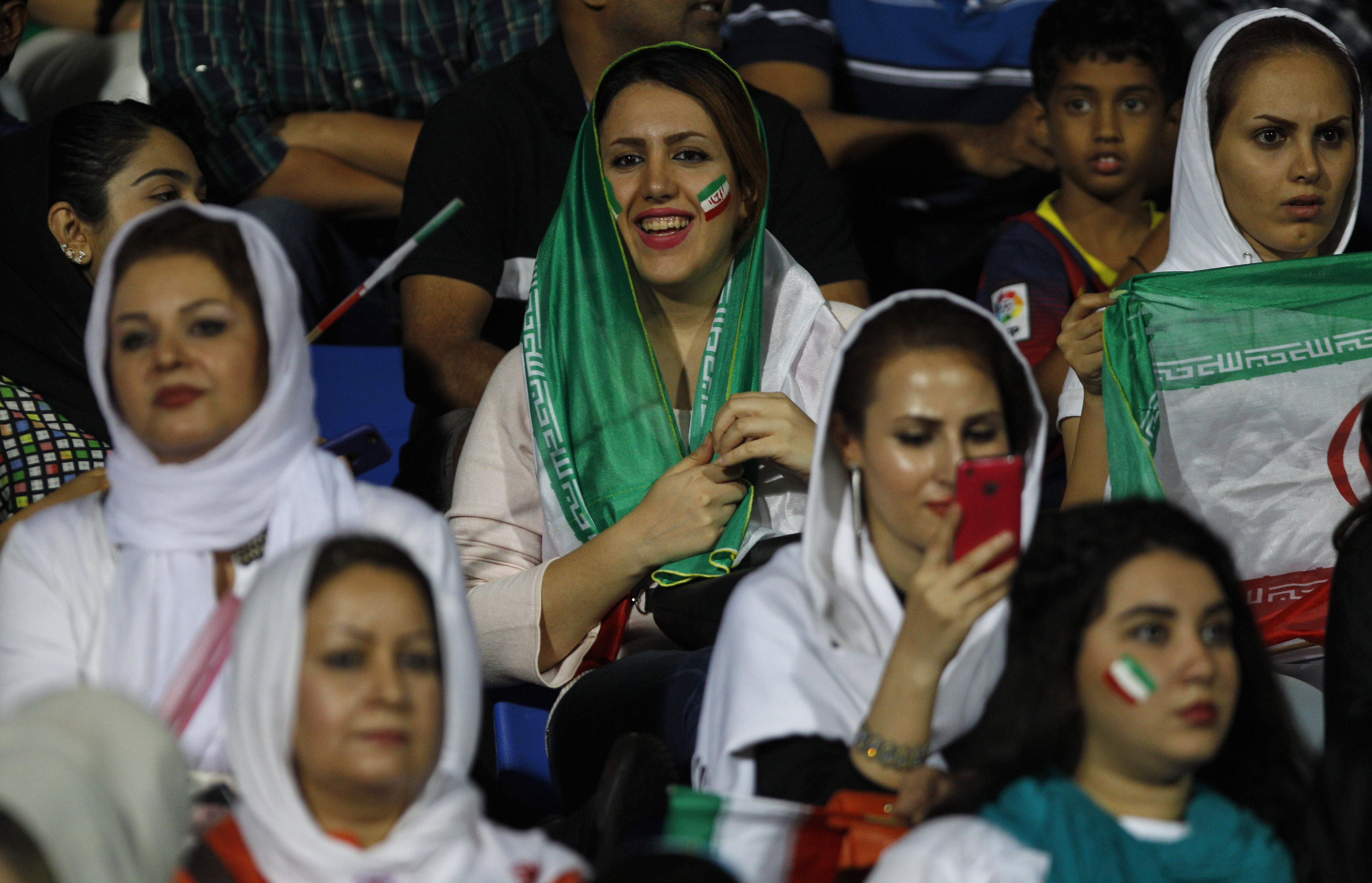 FILE - In this Sept. 8, 2015 file photo, Iranian women watch the 2018 FIFA World Cup qualifying soccer match between Iran and India in Bangalore, India.   Iranian women are being denied their place inside sports venues again, with no way to watch their Ol