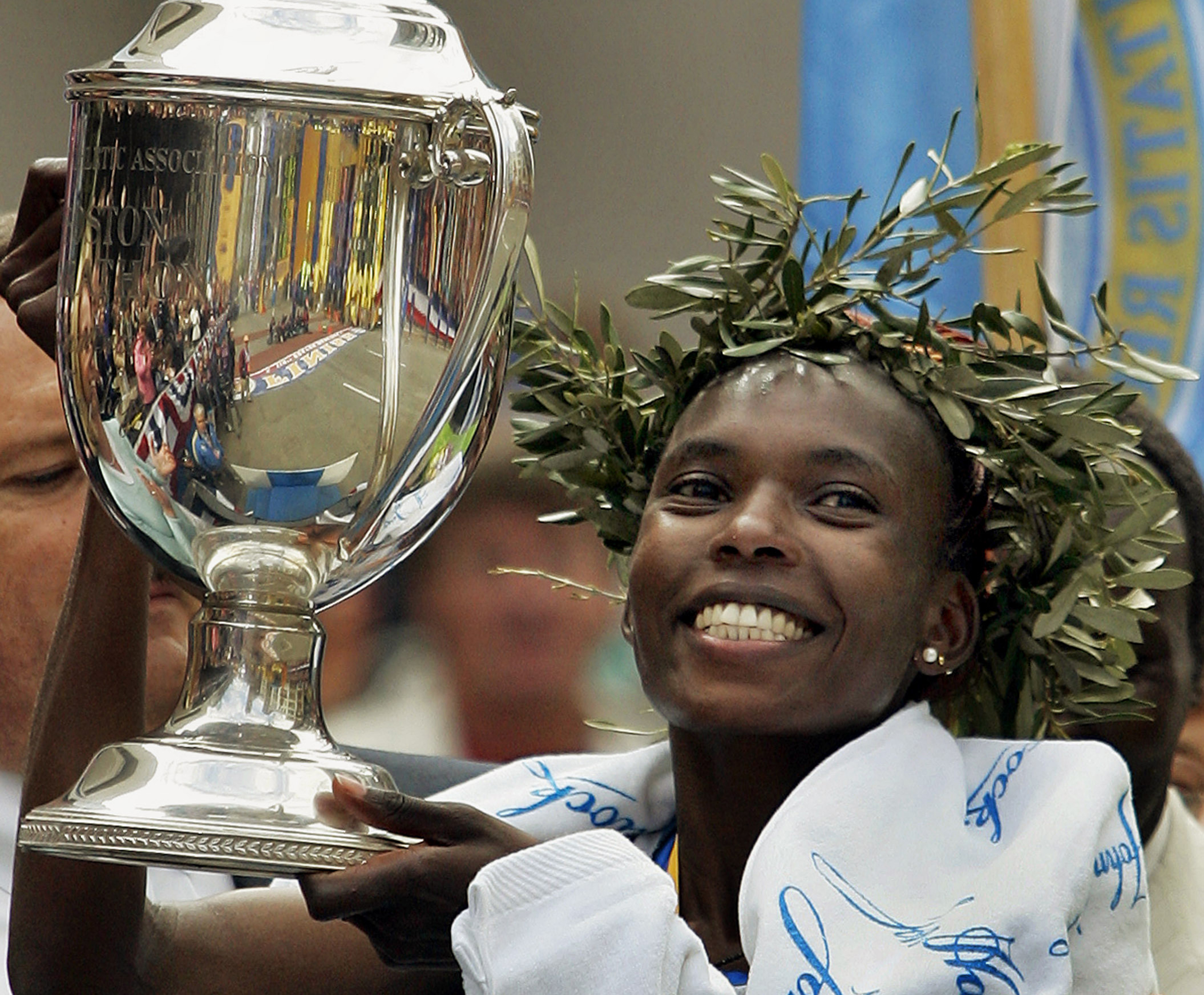FILE - In this Monday, April 17, 2006, file photo Rita Jeptoo of Kenya holds the trophy after winning the women's division of the 110th running of the Boston Marathon, in Boston. Kenyan police investigating doping searched the hotel rooms of two Italian a