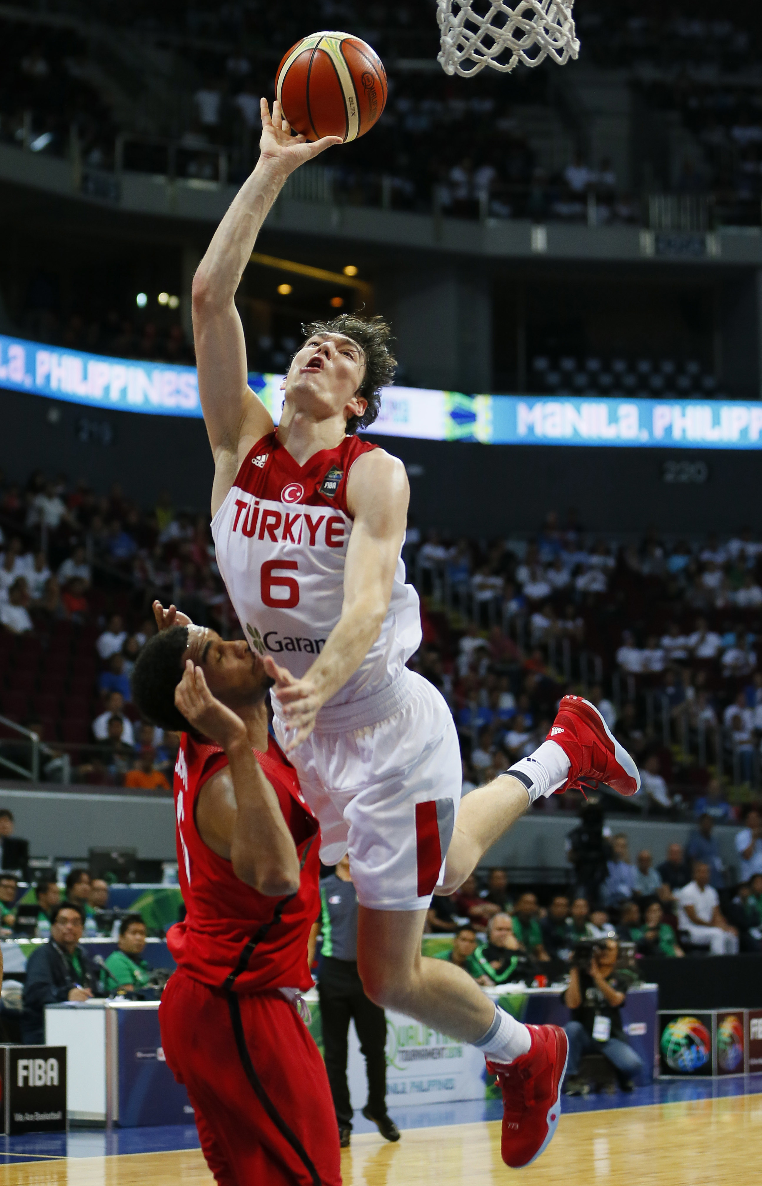 Turkey's Cedi Osman is fouled by Canada's Cory Joseph as the former drives to the basket during the Group A FIBA Olympics Qualifying basketball match Tuesday, July 5, 2016 in suburban Pasay city south of Manila, Philippines. Canada won 77-66.(AP Photo/Bul