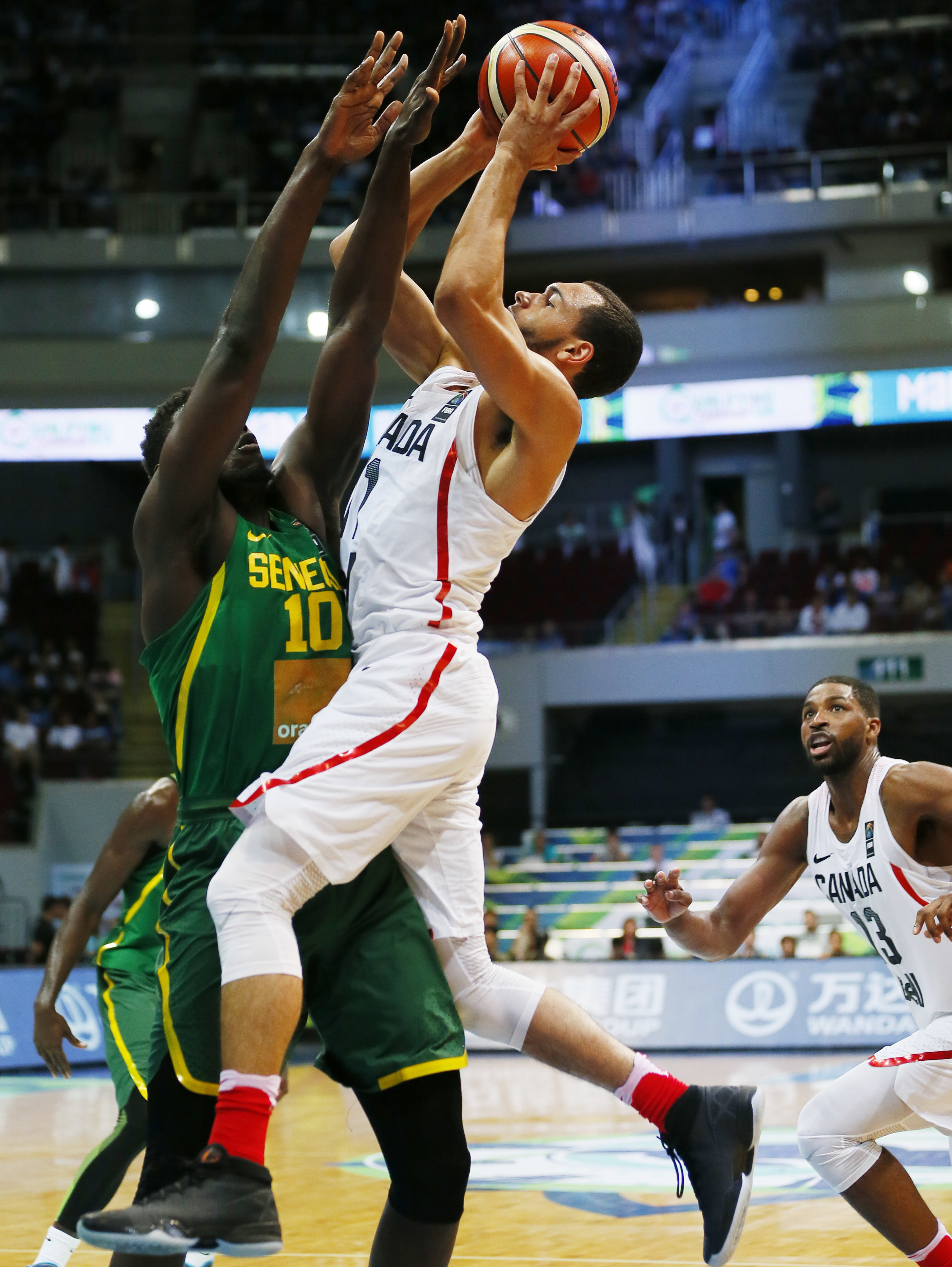 Canada's Tyler Ennis shoots over Senegal's Cheikh Mbodj, left, during the Group A FIBA Olympic Qualifying basketball match Wednesday, July 6, 2016 at the Mall of Asia Arena in suburban Pasay city south of Manila, Philippines. At right is Senegal's Tristan