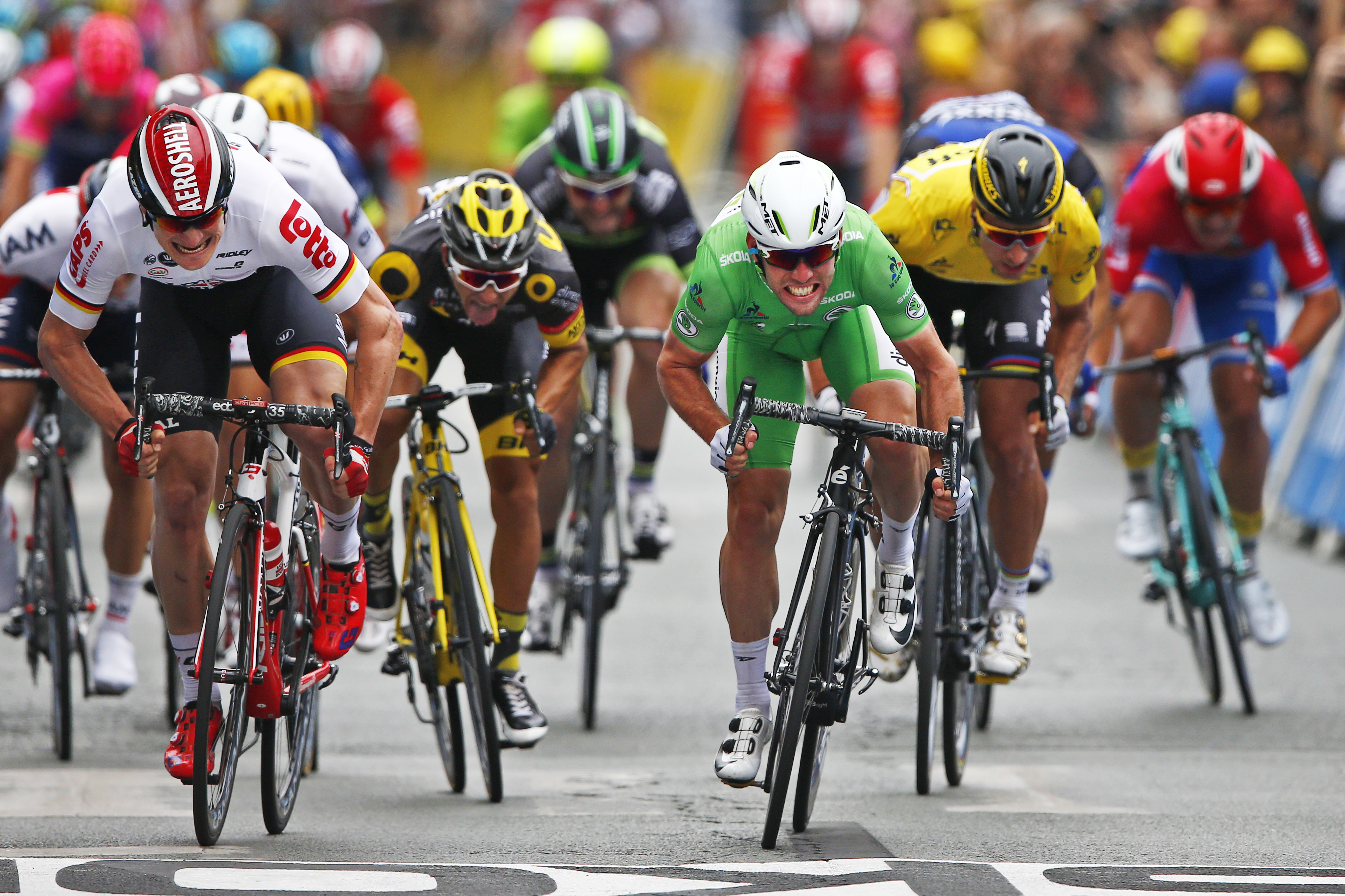 FILE - In this July 4, 2016, file photo, Britain's Mark Cavendish, wearing the best sprinter's green jersey, crosses the finish line ahead of Germany's Andre Greipel, left, and Peter Sagan of Slovakia, wearing the overall leader's yellow jersey, to win th