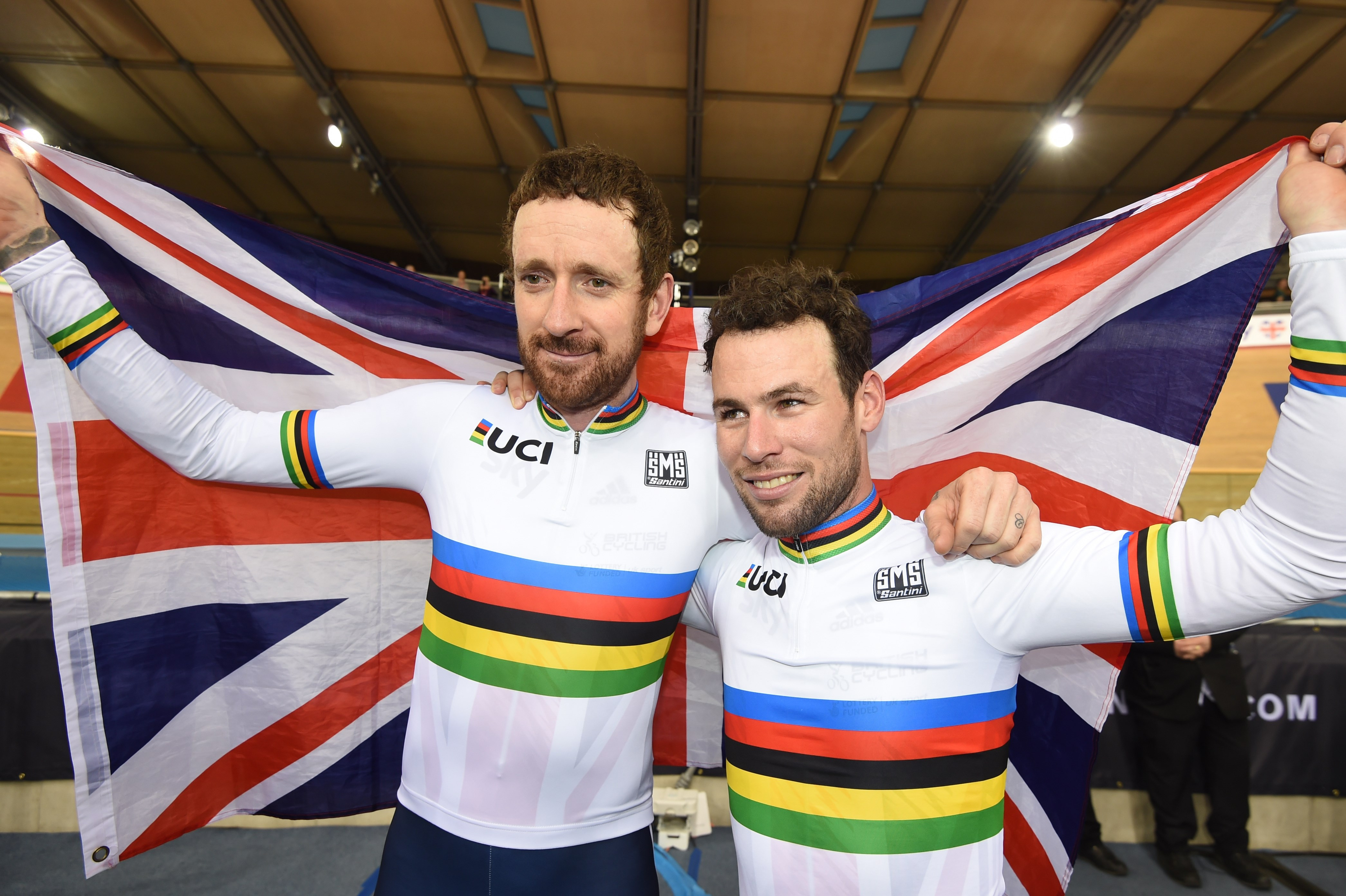 FILE - In this March 6, 2016, file photo, Britain's Bradley Wiggins and Mark Cavendish hold up a British flag as they pose for photographers with their gold medals after winning the Men's Madison race at the World Track Cycling championships at the Lee Va