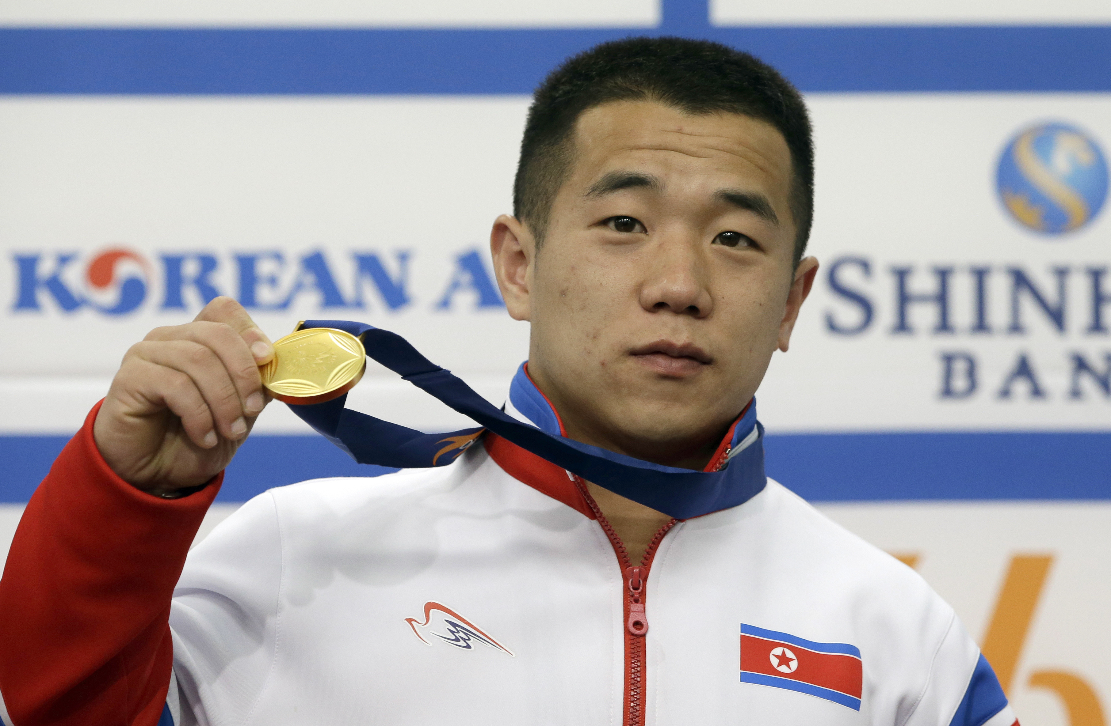 FILE - In this Sept. 23, 2014, file photo, North Korea's gold medalist of the men's 56kg weightlifting Om Yun Chol poses with his gold medal during a press conference at the 17th Asian Games in Incheon, South Korea. Om Yun-chol is the front-runner to win