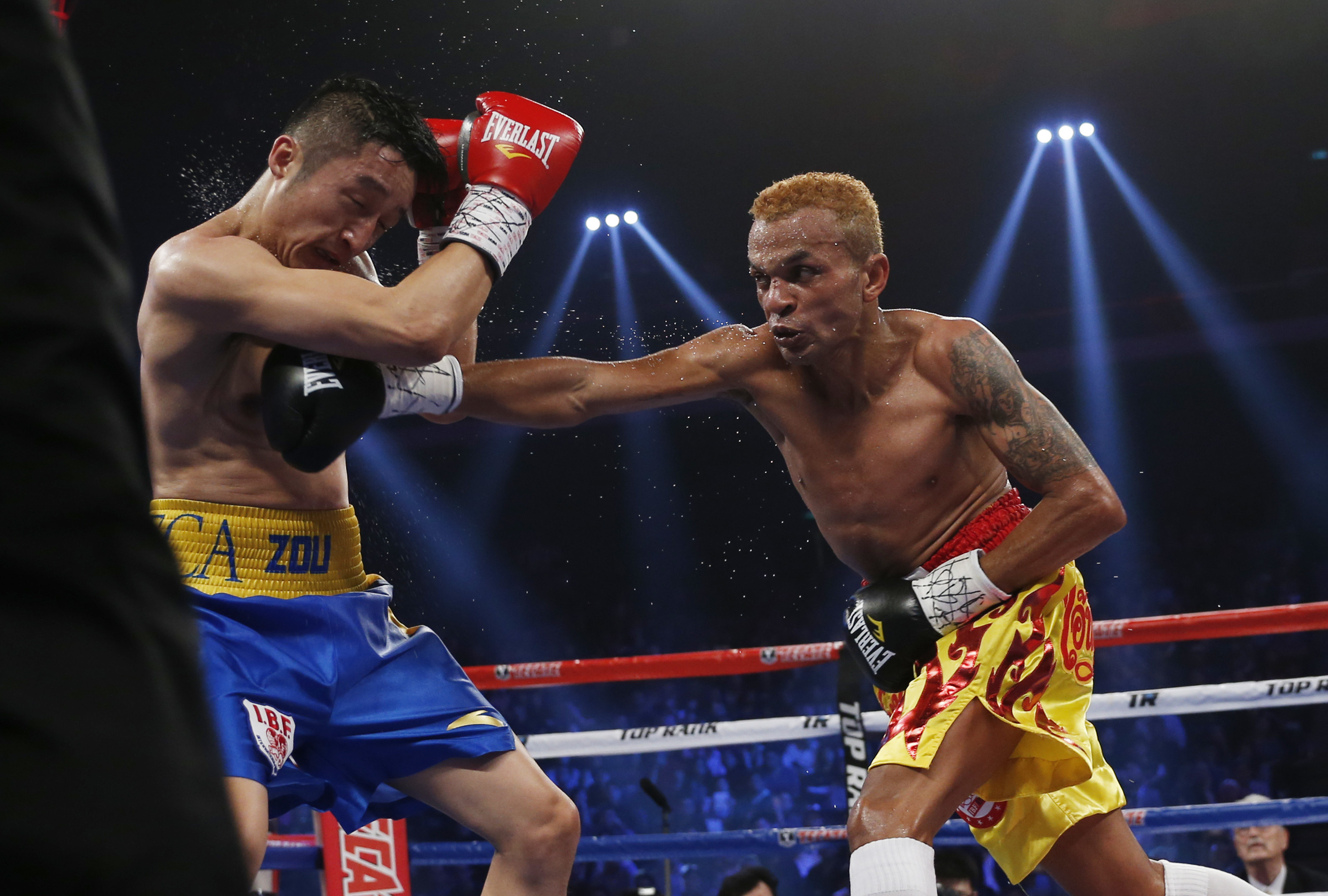 FILE - In this March 7, 2015, file photo, Thailand's Amnat Ruenroeng, right, throws a punch at China's double Olympic gold medalist Zou Shiming during their IBF flyweight title boxing match at the Venetian Macao in Macau. The International Boxing Associat