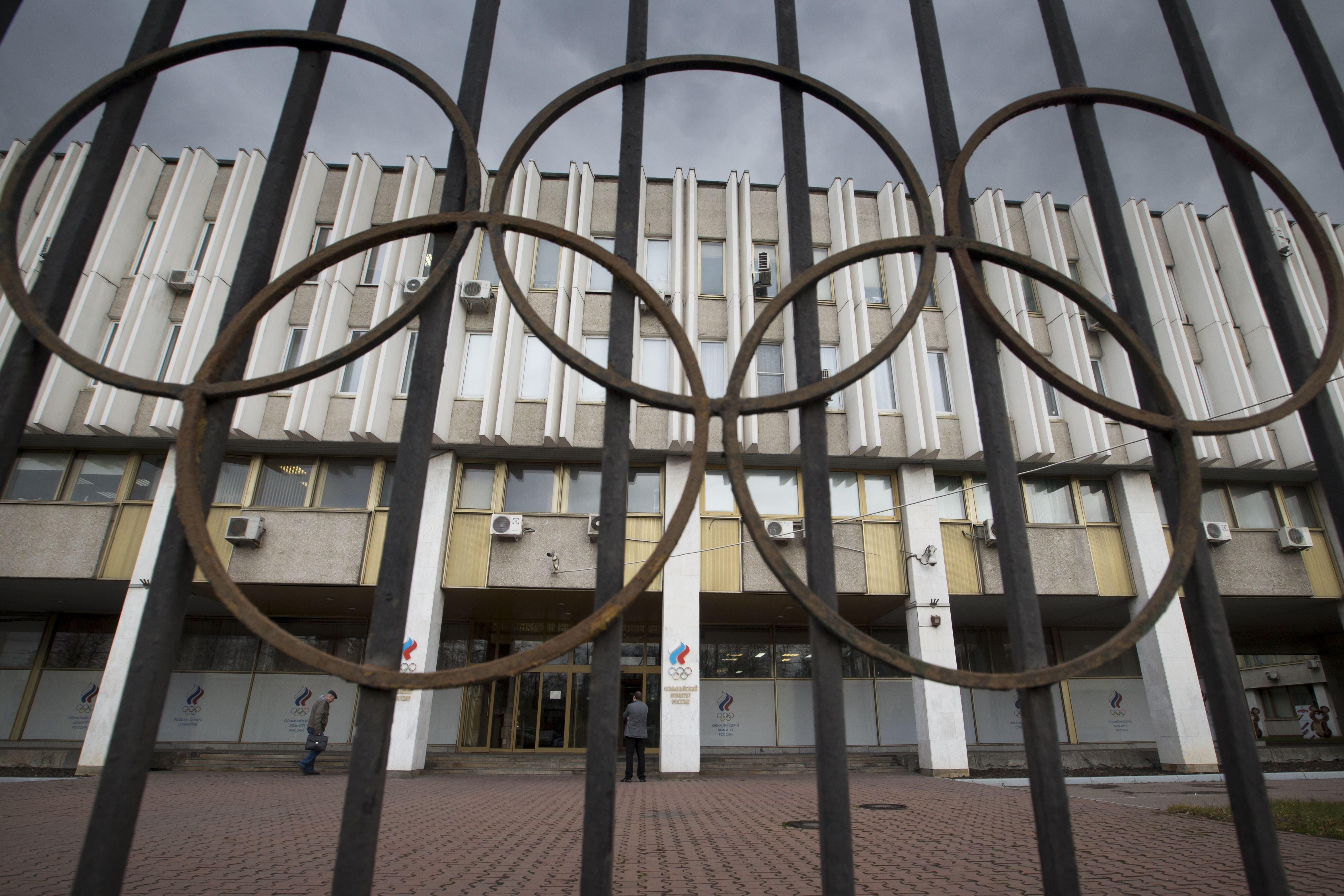FILE - In this Nov. 13, 2015, file photo people walk in front of the Russian Olympic Committee building in Moscow. On Monday, July 18, 2016 WADA investigator Richard McLaren confirmed claims of state-run doping in Russia. (AP Photo/Pavel Golovkin, File)