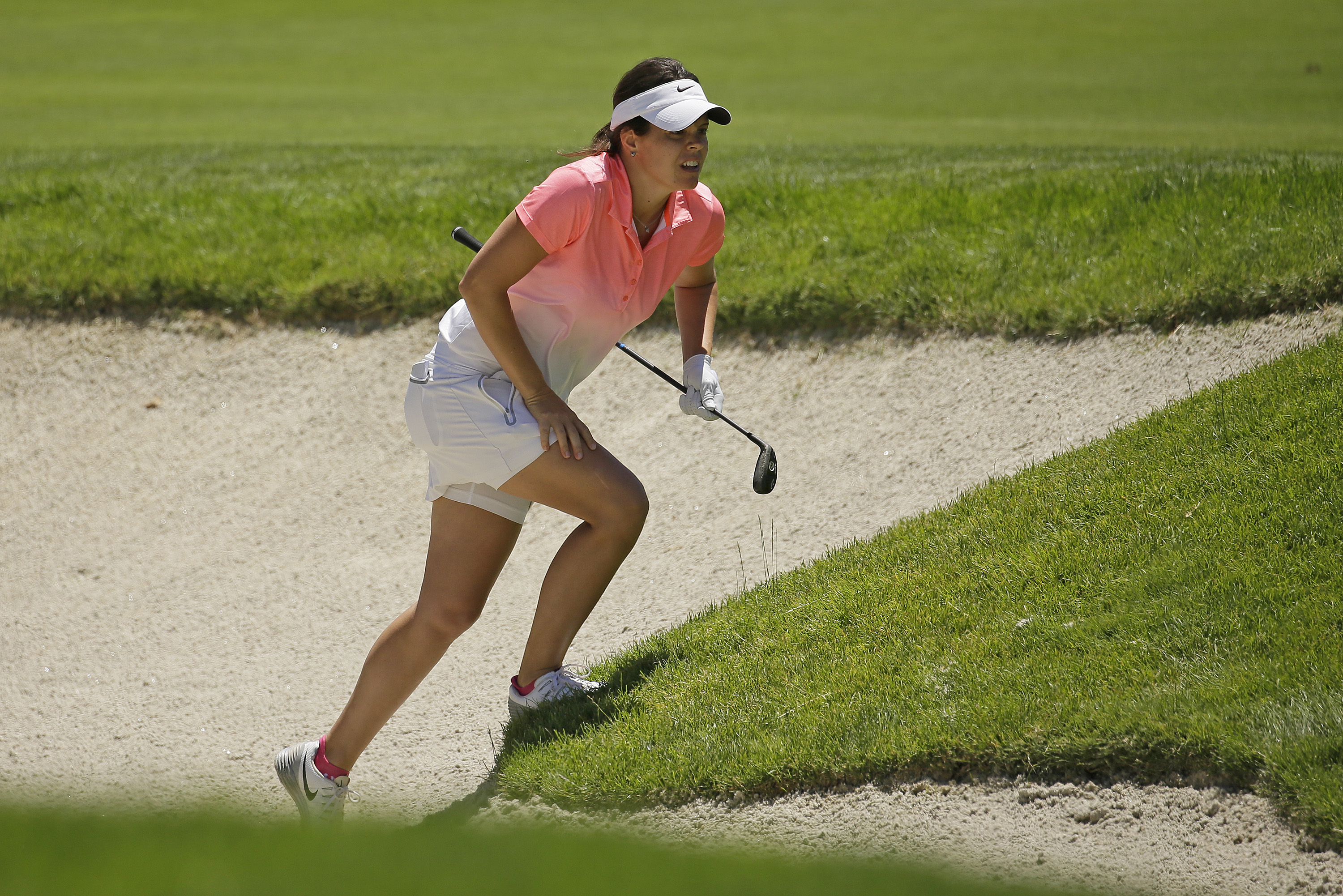 In this Thursday, July 7, 2016, Miriam Nagl, of Brazil, follows her shot out of a bunker on the 10th fairway during the first round of the U.S. Women's Open golf tournament at CordeValle in San Martin, Calif. Many foreigners are taking advantage of Brazil