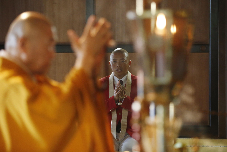 In this Saturday, July 16, 2016 photo, Kazuki Yazawa, right, canoe slalom Olympian and Buddhist priest, joins his hands in prayer while Kansho Kayaki, deputy chief priest, offers prayers during a Buddhist ritual at Zenkoji Daikanjin Temple in Nagano, Japa