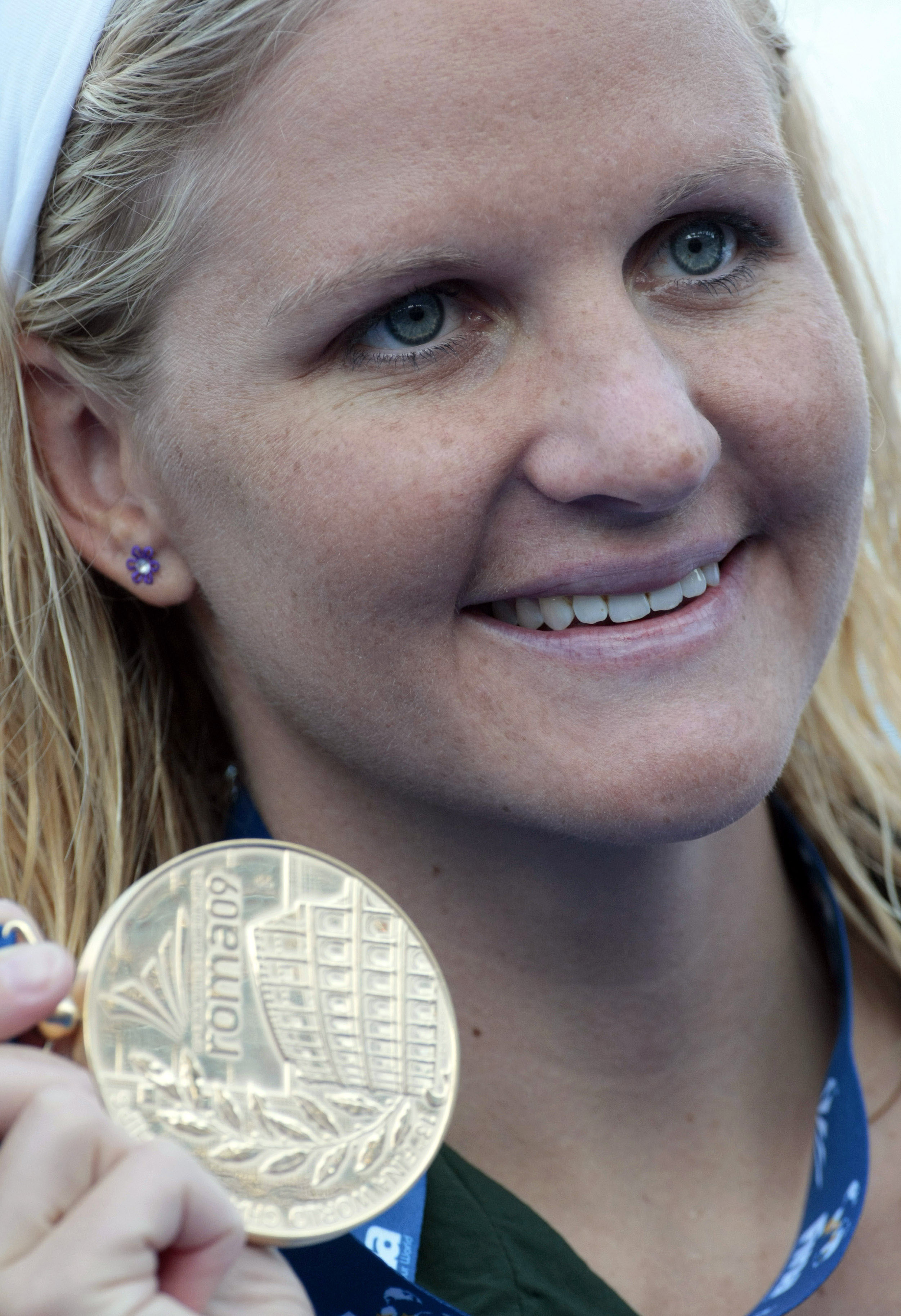 File- In this Aug. 1, 2009, file photo Zimbabwe's Kirsty Coventry holds the gold medal she won in the final of the women's 200-meter backstroke, at the FINA Swimming World Championships in Rome. Like Michael Phelps, Coventry is going to the Olympics for t