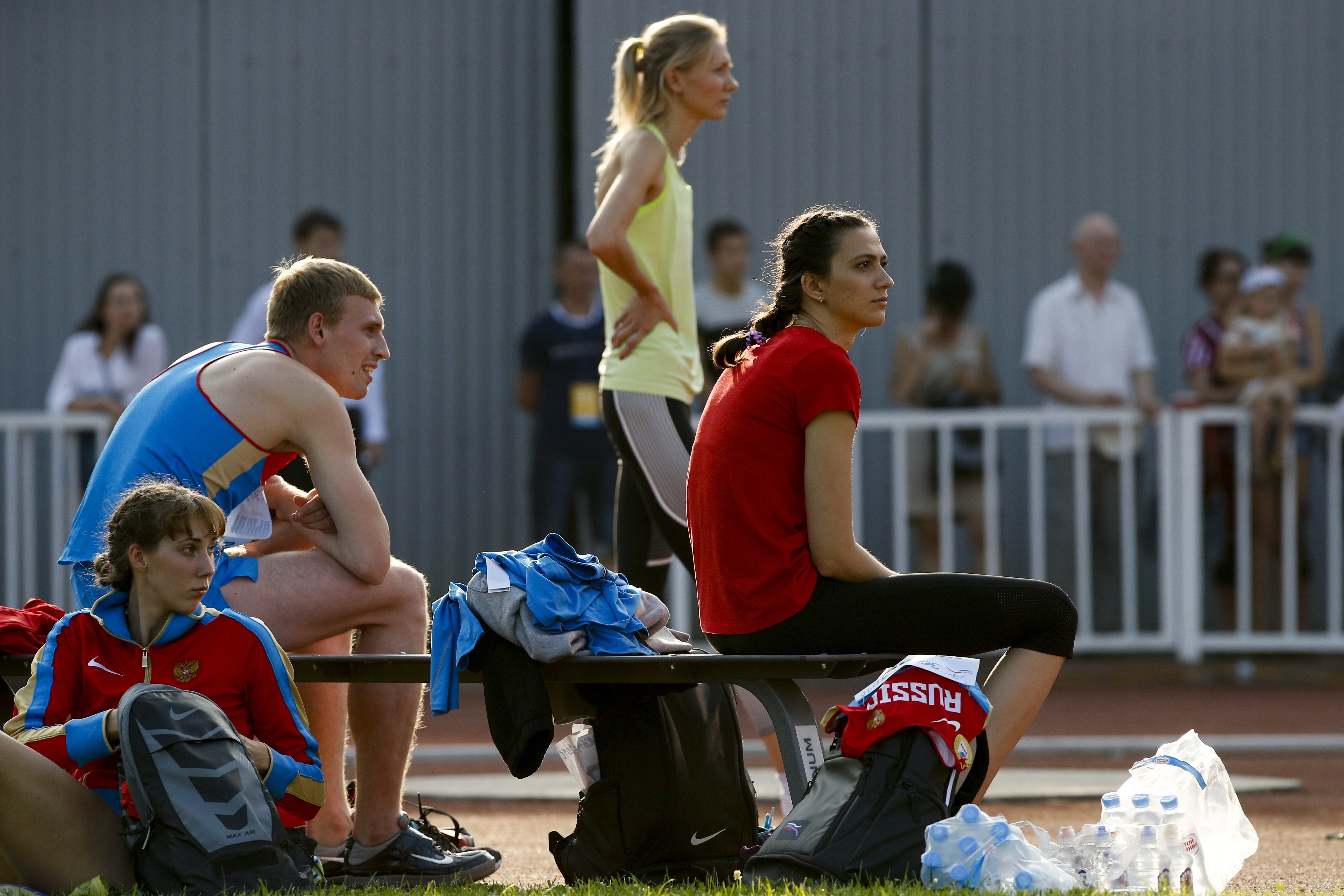 World Championships gold medalist Mariya Kuchina, right, rests with the other Russian athletes as she waits to make an attempt in the women's high jump during the Russian Stars 2016 track and field competitions in Moscow, Russia, Thursday, July 28, 2016.