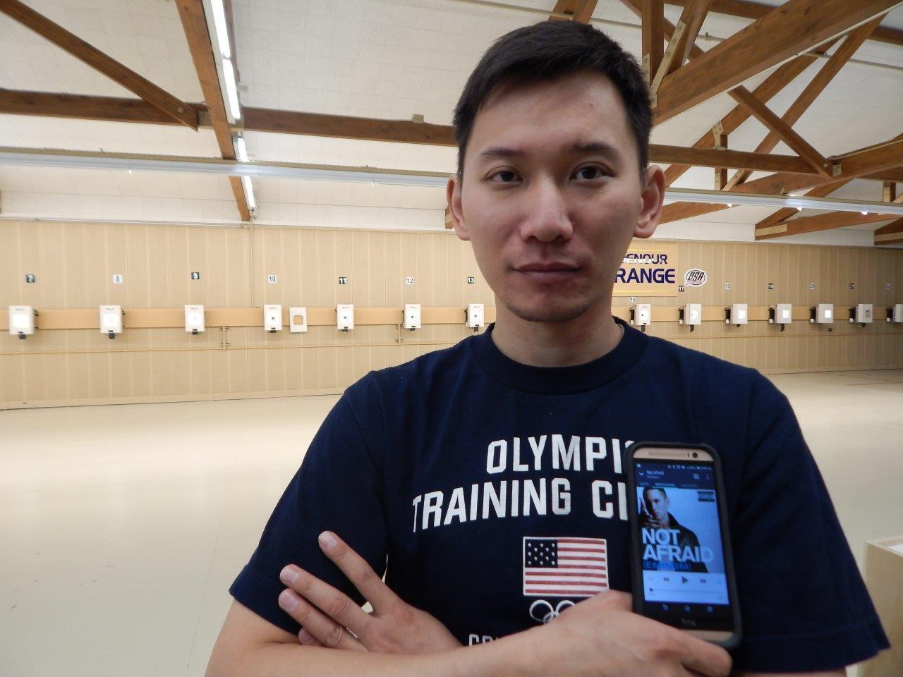 In this July 26, 2016, image provided by USA Shooting, Jay Shi poses at a shooting range in Colorado Springs, Colo., with Eminem on his phone. The Associated Press asked several Olympians what is the most important thing that youre packing in your bag for