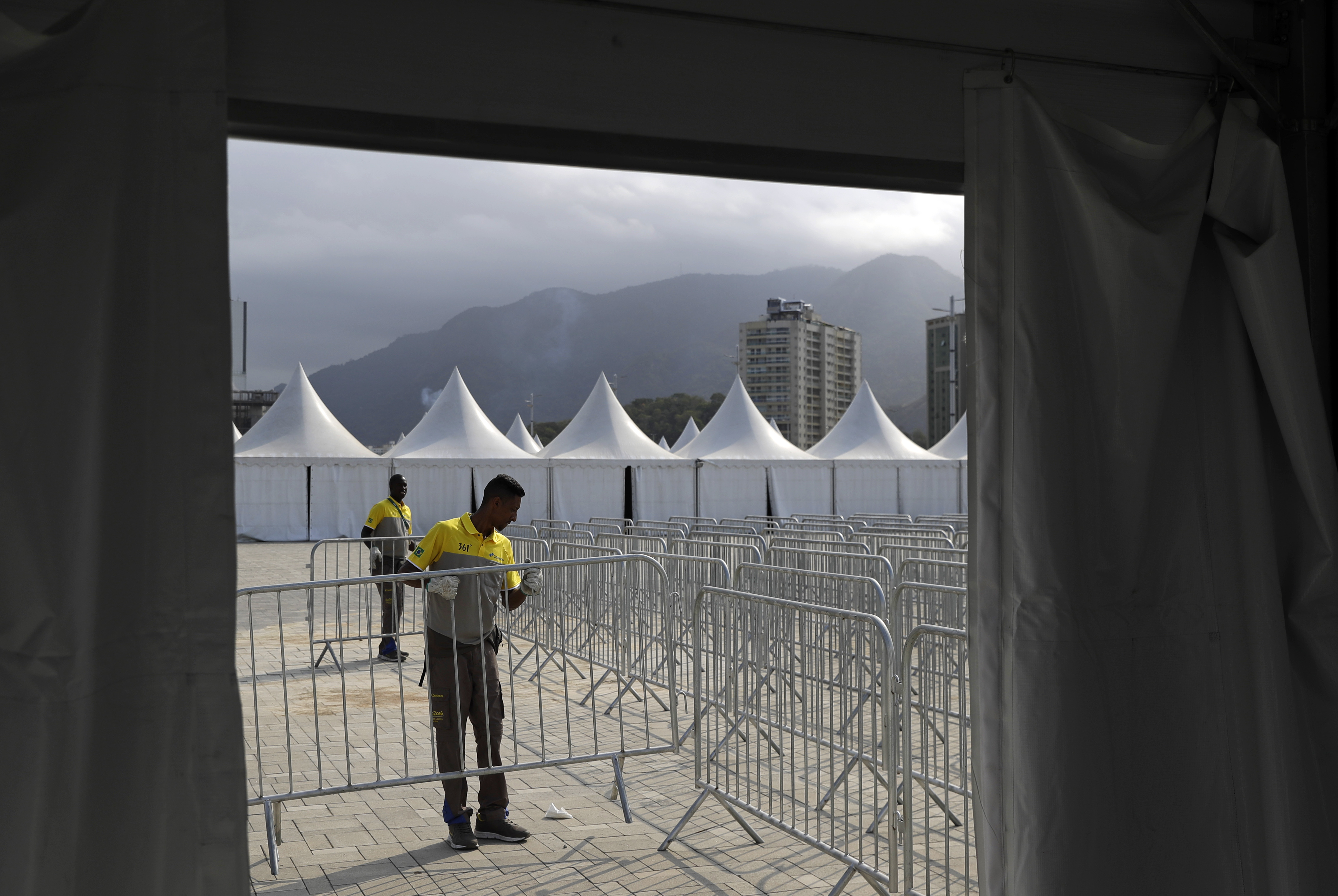 Workers install barricades in preparation for the 2016 Rio de Janeiro Games inside Olympic Park in Rio de Janeiro, Brazil, Friday, July 29, 2016. (AP Photo/Patrick Semansky)