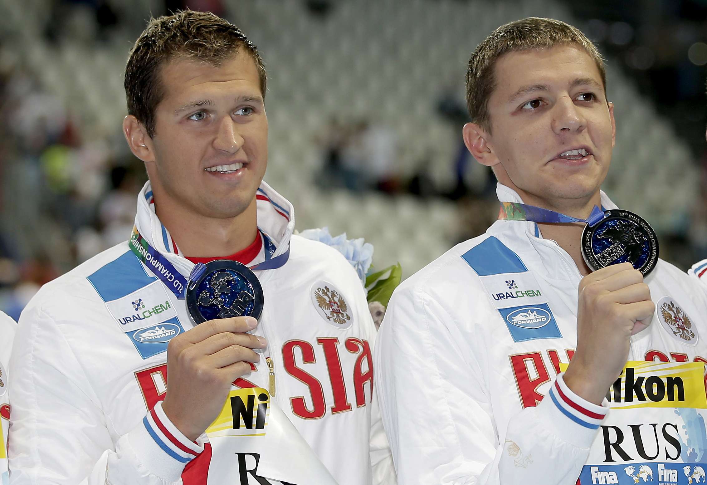 FILE - In this Aug. 2, 2015, file photo, Russian swimmers Nikita Lobintsev, left, and Vladimir Morozov hold up their silver medals at the Swimming World Championships in Kazan, Russia. FINA says three more swimmers were identified by World Anti-Doping Age