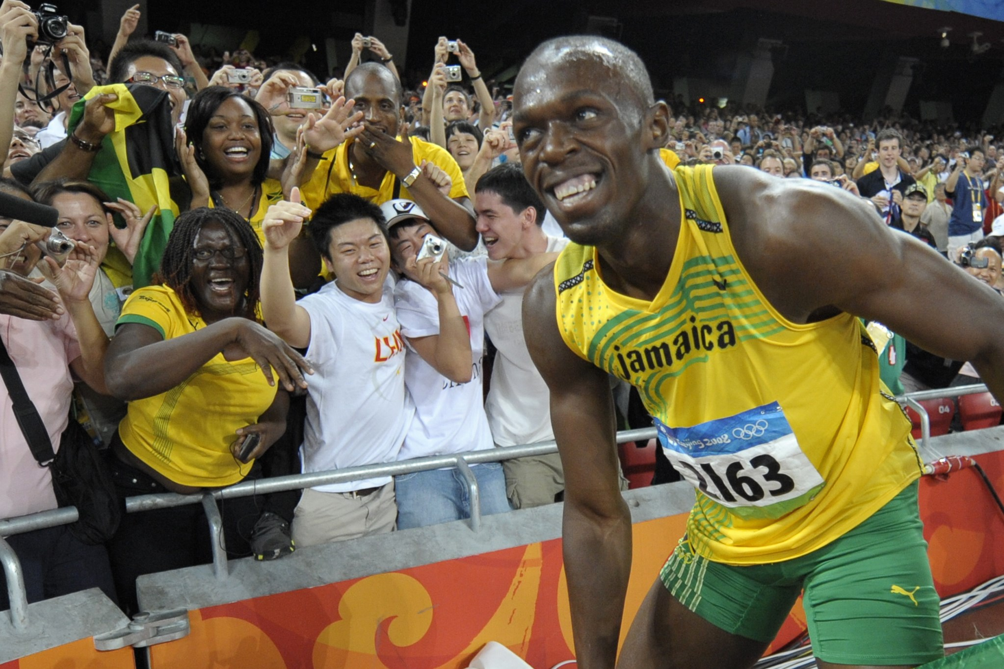 FILE - In this Aug. 16, 2008, file photo, Usain Bolt of Jamaica smiles at cheering spectators after winning the men's 100-meter final with a world record in the National Stadium at the Beijing 2008 Olympics in Beijing. Since he coasted to the 100-meter fi