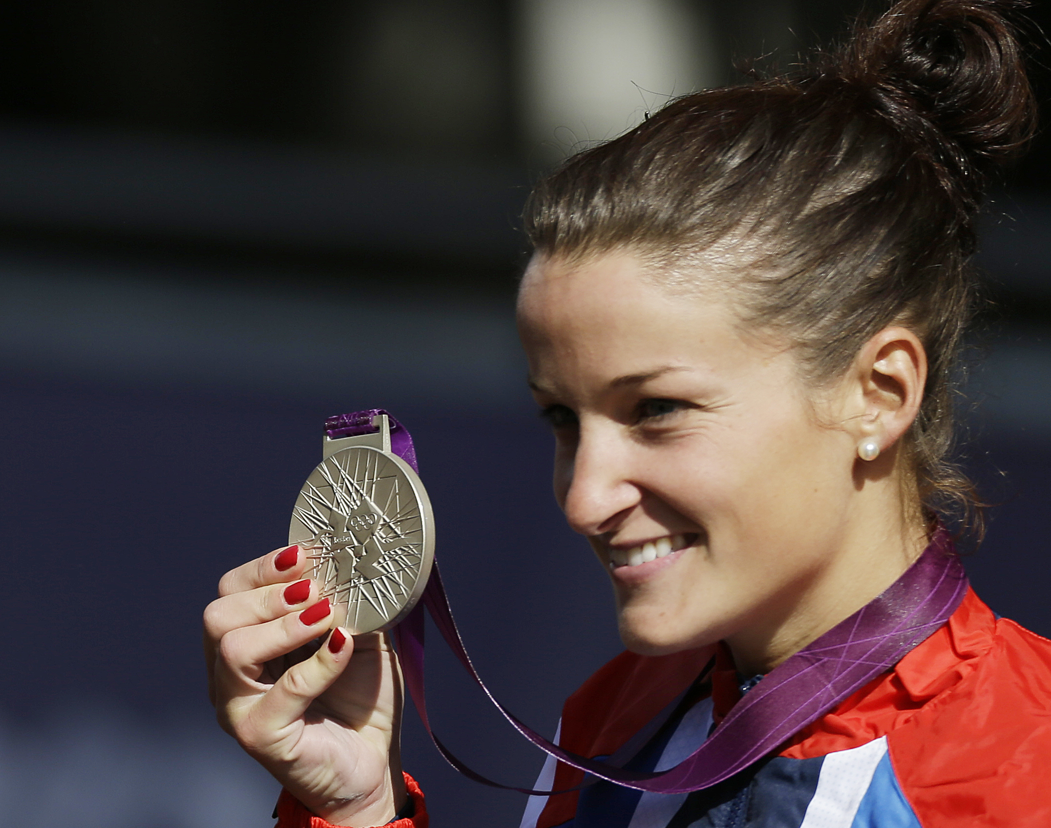 FILE - This is a Sunday, July 29, 2012,  file photo of Britain's Lizzie Armitstead holds the silver medal as she celebrates during the medal ceremony in the Women's Road Cycling race at the 2012 Summer Olympics in London.  Armitstead won an appeal against