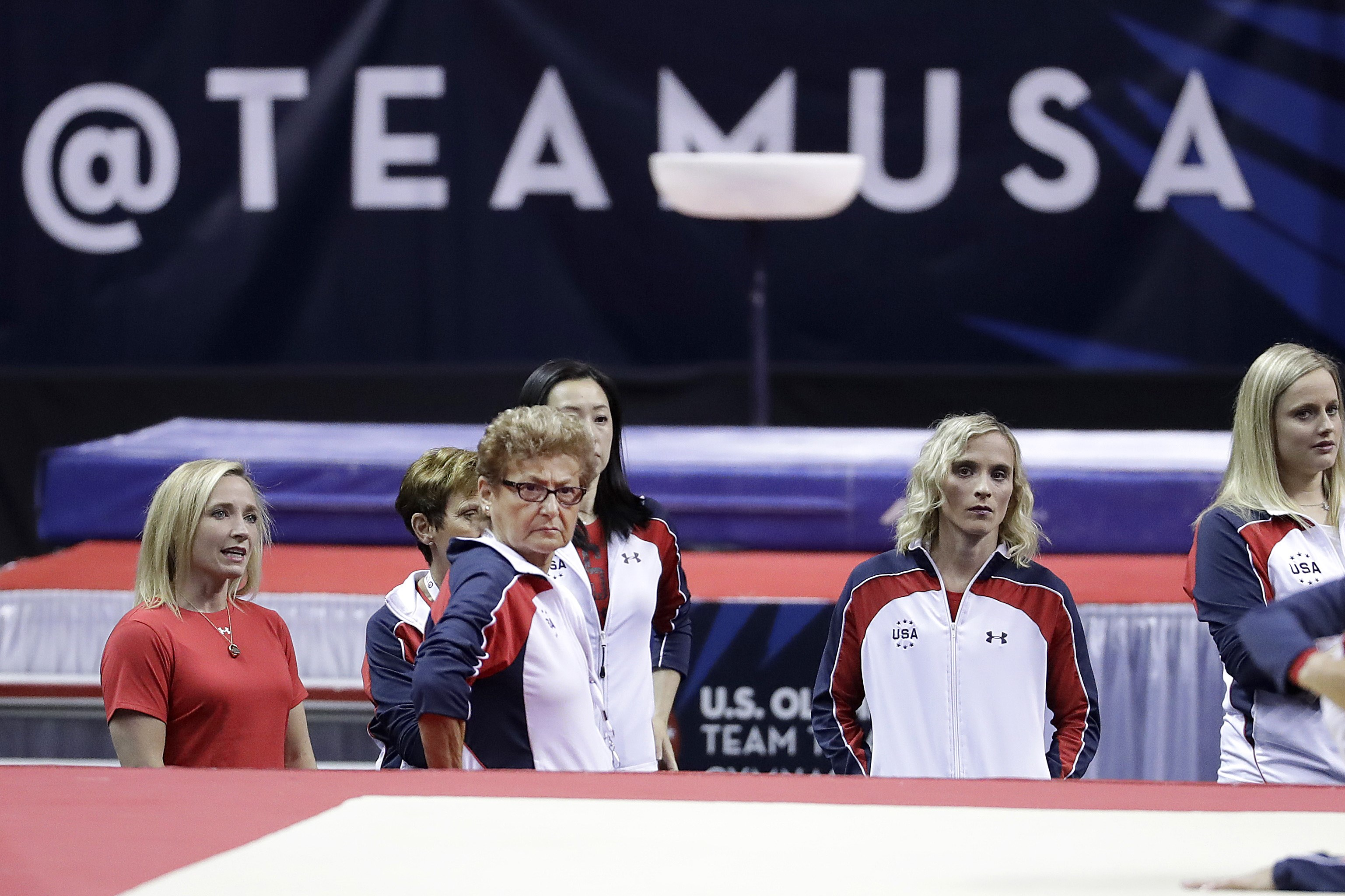 Marta Karolyi, national team coordinator for USA Gymnastics, center left, watches as competitors warm up before the women's U.S. Olympic gymnastics trials in San Jose, Calif., Sunday, July 10, 2016. (AP Photo/Gregory Bull)